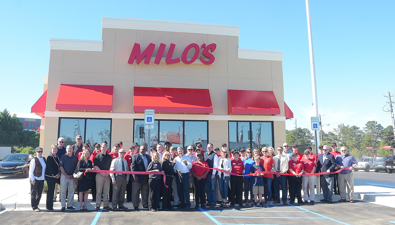 Milo's Hamburgers CEO Tom Dekle cuts a ribbon Tuesday afternoon to officially open the popular hamburger restaurant's newest location in Jasper. Looking on are Milo's officials and employees and members of the Chamber of Commerce of Walker County. Daily Mountain Eagle - Ron Harris