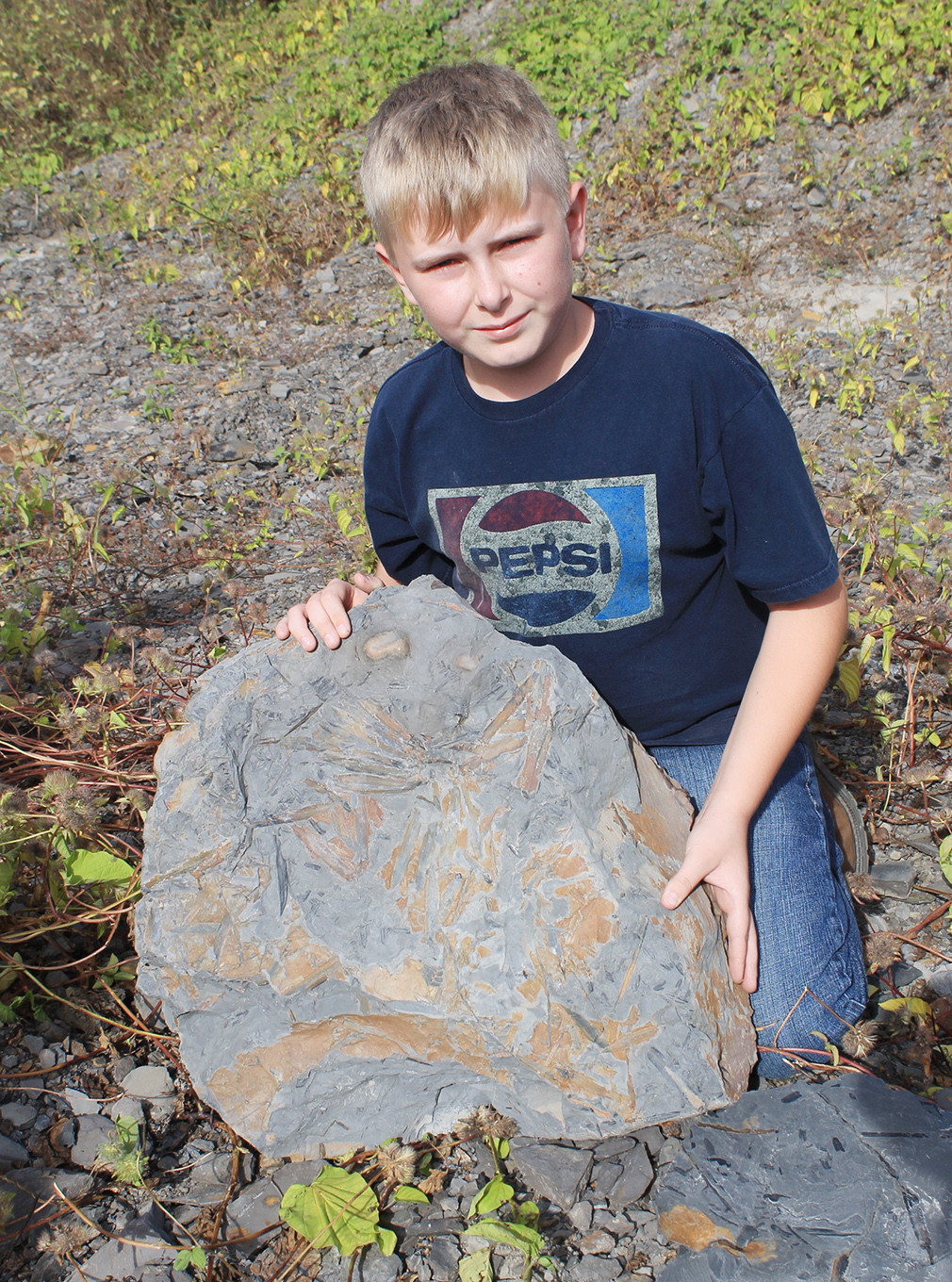 Camden Davis, 12, of Jasper, poses with the fossils he found at the Steven C. Minkin Paleozoic Footprint Site in Union Chapel on Oct. 14. The fossil has been removed from the site and will become part of the McWane Center's collection.  Daily Mountain Eagle - Jennifer Cohron