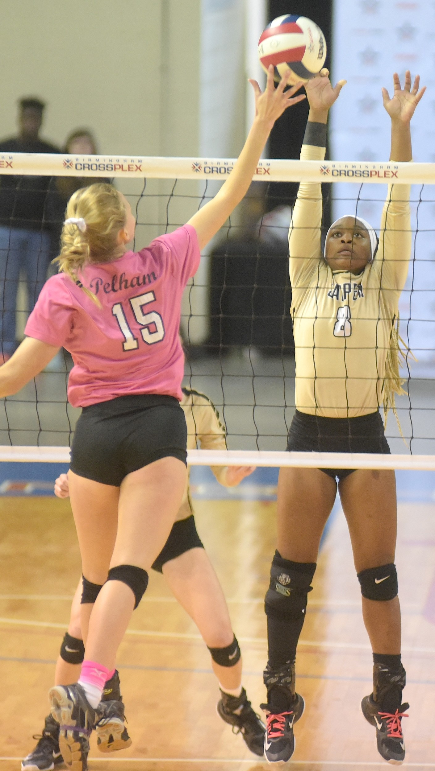 Jasper's Tameyah Griffin (8) tries to block the spike from Pelham's Emorie Long (15) during the Class 6A state championship match in Birmingham on Thursday.