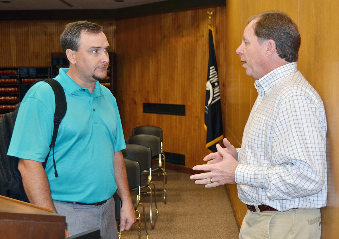County Engineer Mike Short, right, speaks after Monday's Walker County Commission meeting with AT&T territory manager Shad Molck about the new lease agreement with the county. The county's new AT&T phone system will provide better service and will save the county ten's of thousands of dollars each year.
