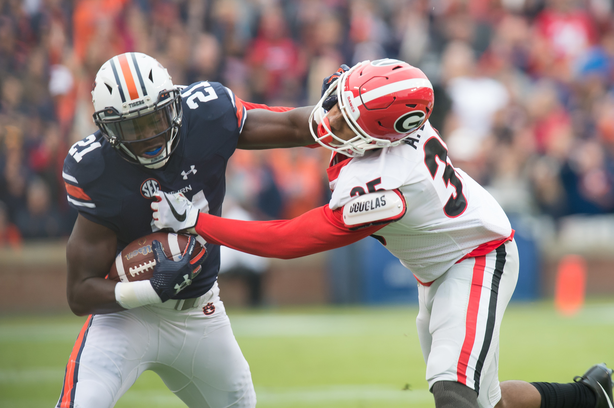 Auburn Tigers running back Kerryon Johnson (21) stiff arms Georgia Bulldogs defensive back Aaron Davis (35) during the first half of Saturday's game, at Jordan-Hare Stadium.