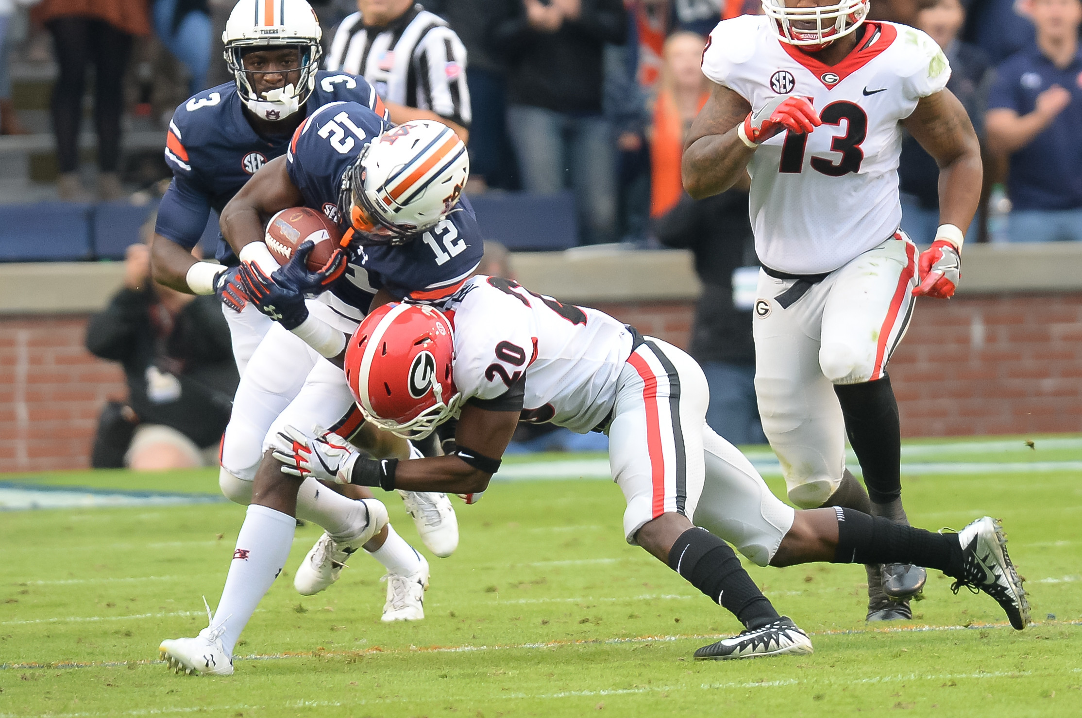 Auburn Tigers wide receiver Eli Stove (12) is tackled by Georgia Bulldogs defensive back J.R. Reed (20) during the first half of Saturday's game, at Jordan-Hare Stadium.