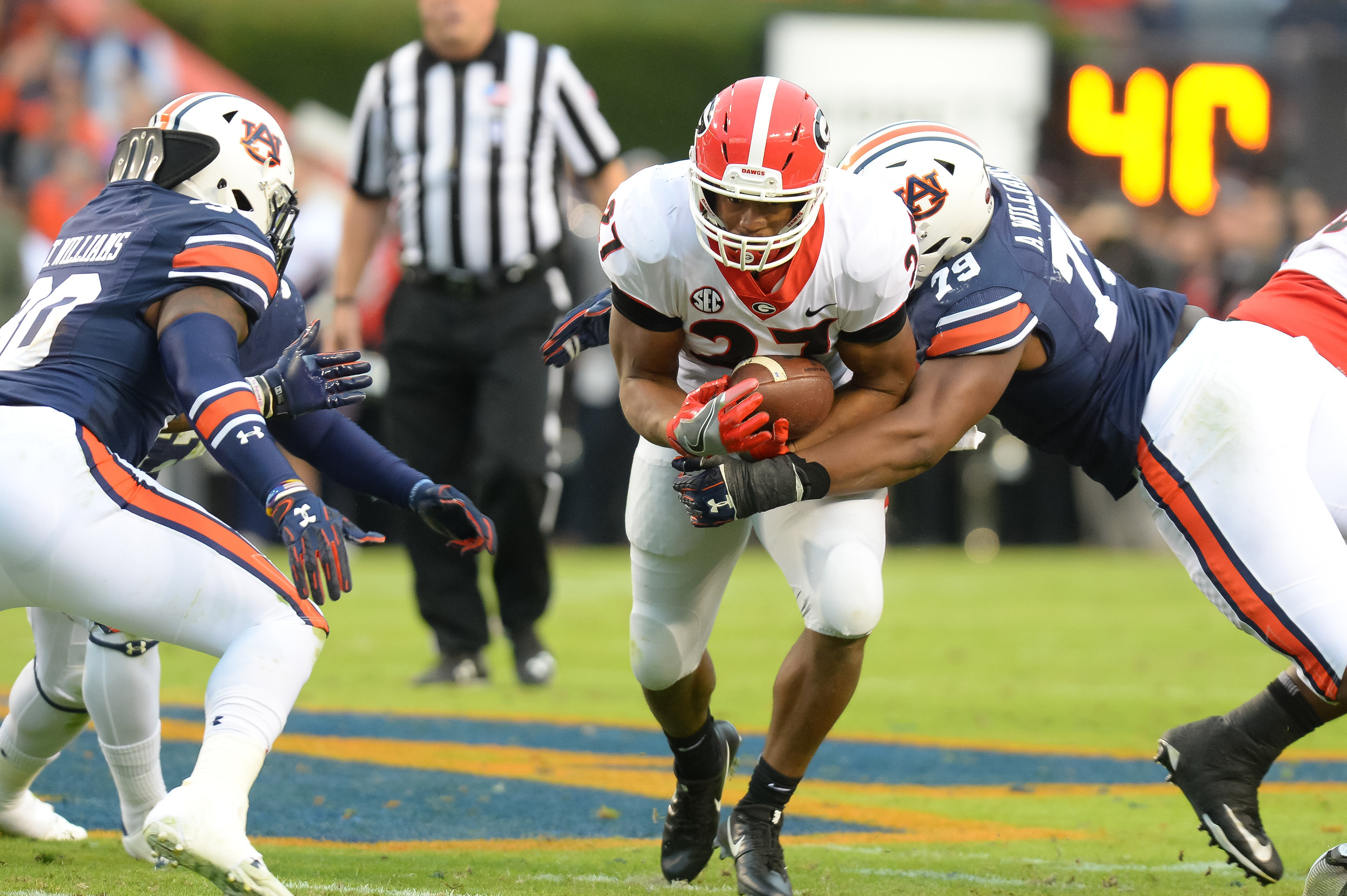 Georgia Bulldogs running back Nick Chubb (27) is tackled by Auburn Tigers defensive lineman Andrew Williams (79) during the first half of Saturday's game, at Jordan-Hare Stadium.