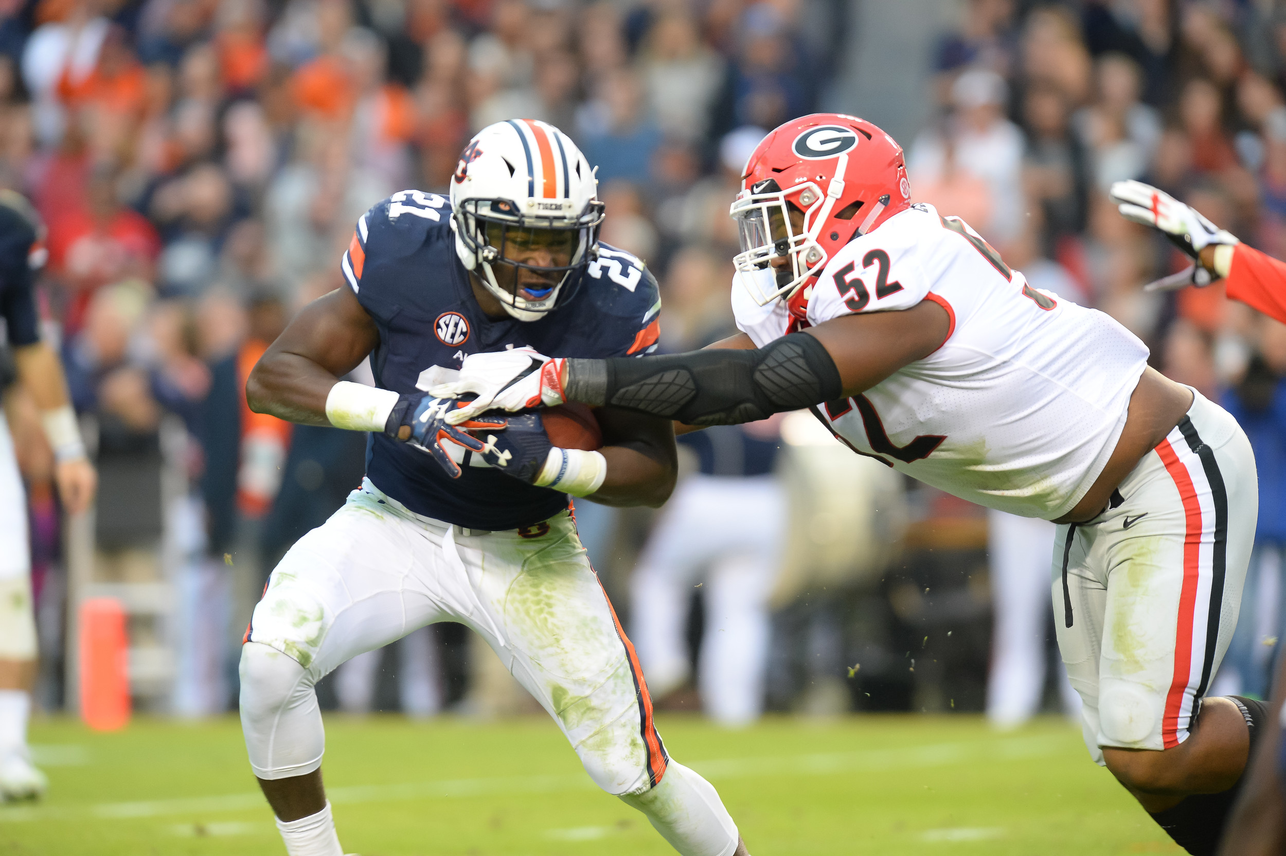 Auburn Tigers running back Kerryon Johnson (21) is tackled by Georgia Bulldogs defensive lineman Tyler Clark (52) during the first half of Saturday's game, at Jordan-Hare Stadium.