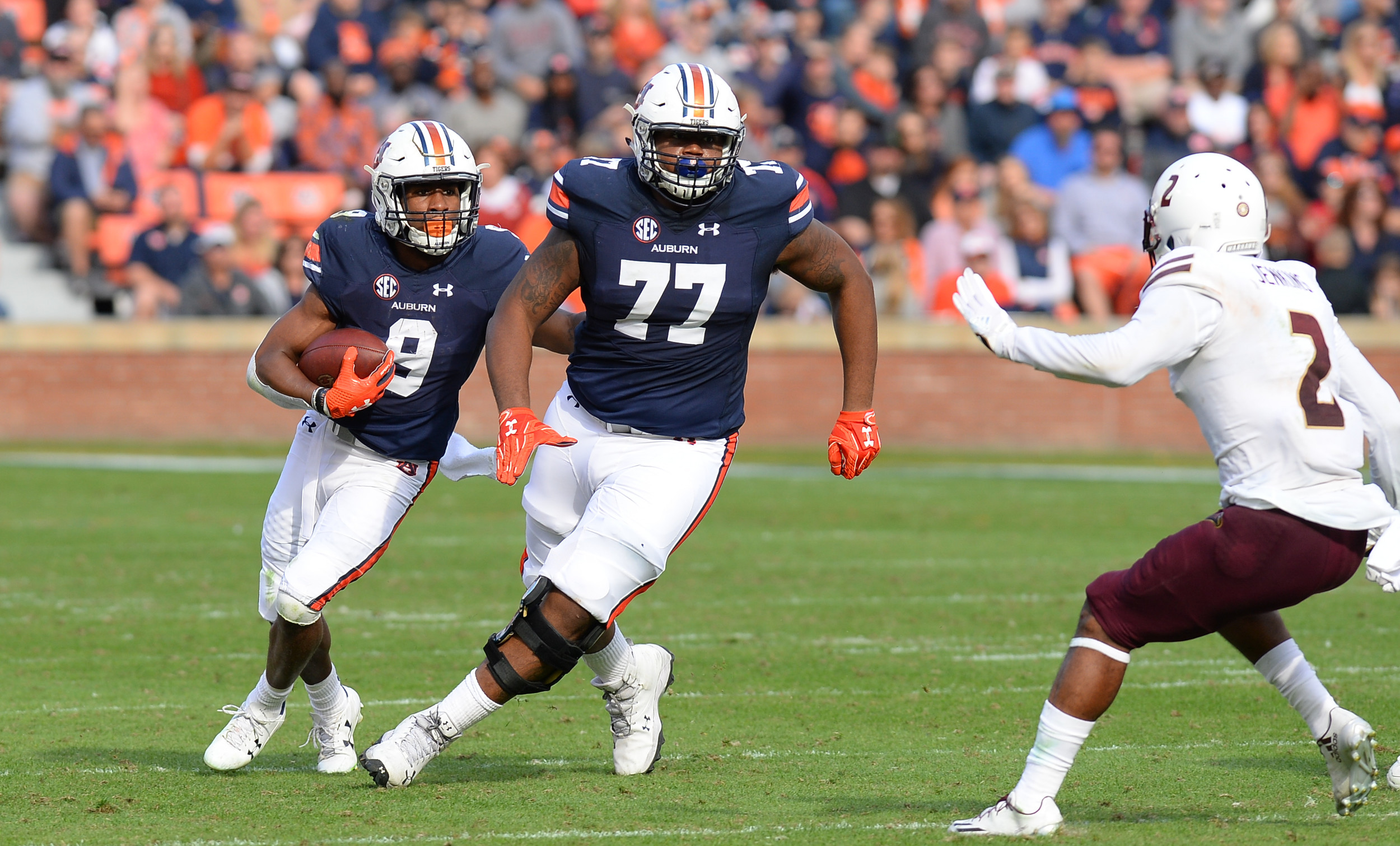 Auburn Tigers running back Kam Martin (9) runs behind  offensive lineman Marquel Harrell (77) during the second half of Saturday's game, at Jordan-Hare Stadium.
