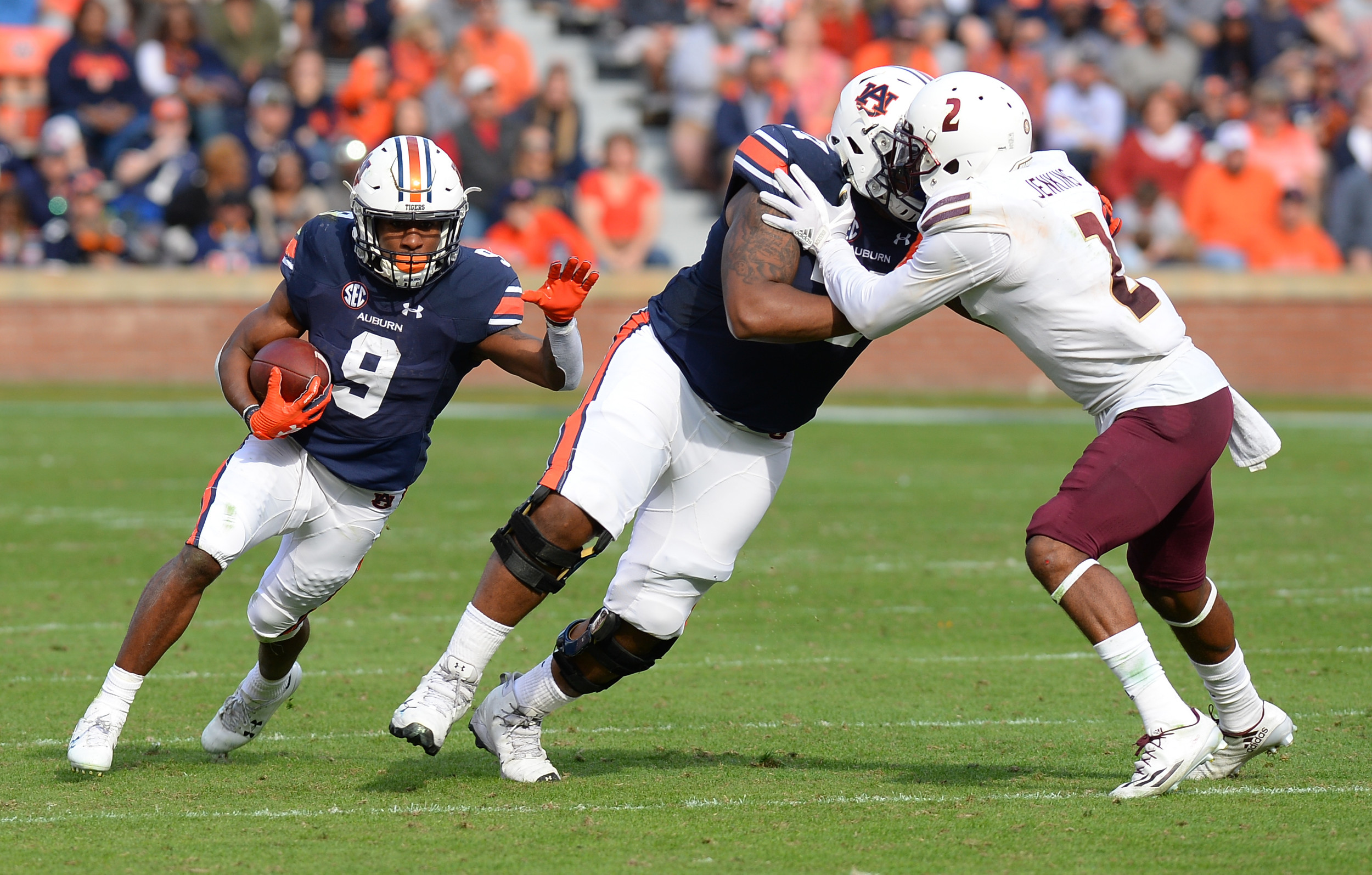 Auburn Tigers running back Kam Martin (9) runs behind the block of offensive lineman Marquel Harrell (77) during the second half of Saturday's game, at Jordan-Hare Stadium.