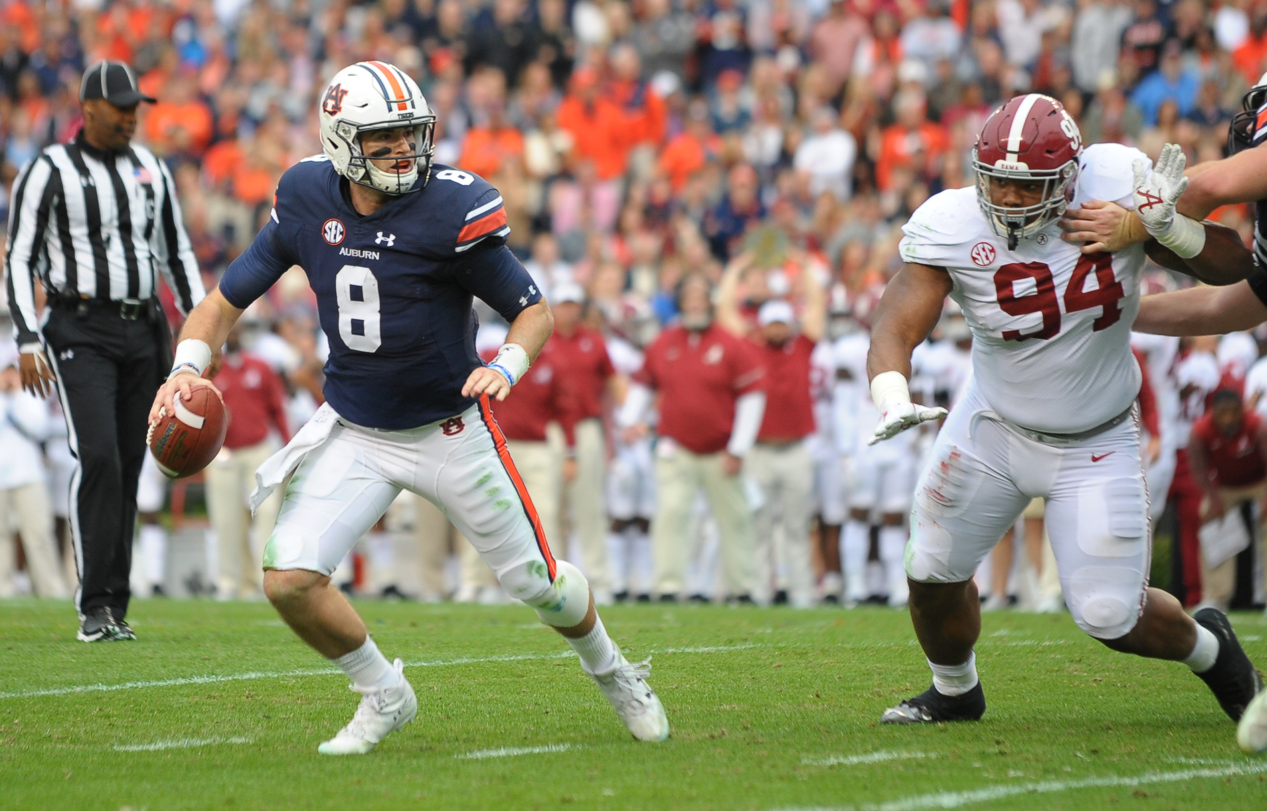 Auburn Tigers quarterback Jarrett Stidham (8) runs away from Alabama Crimson Tide defensive lineman Da'Ron Payne (94) during the first half of Saturday's game, at Jordan-Hare Stadium.