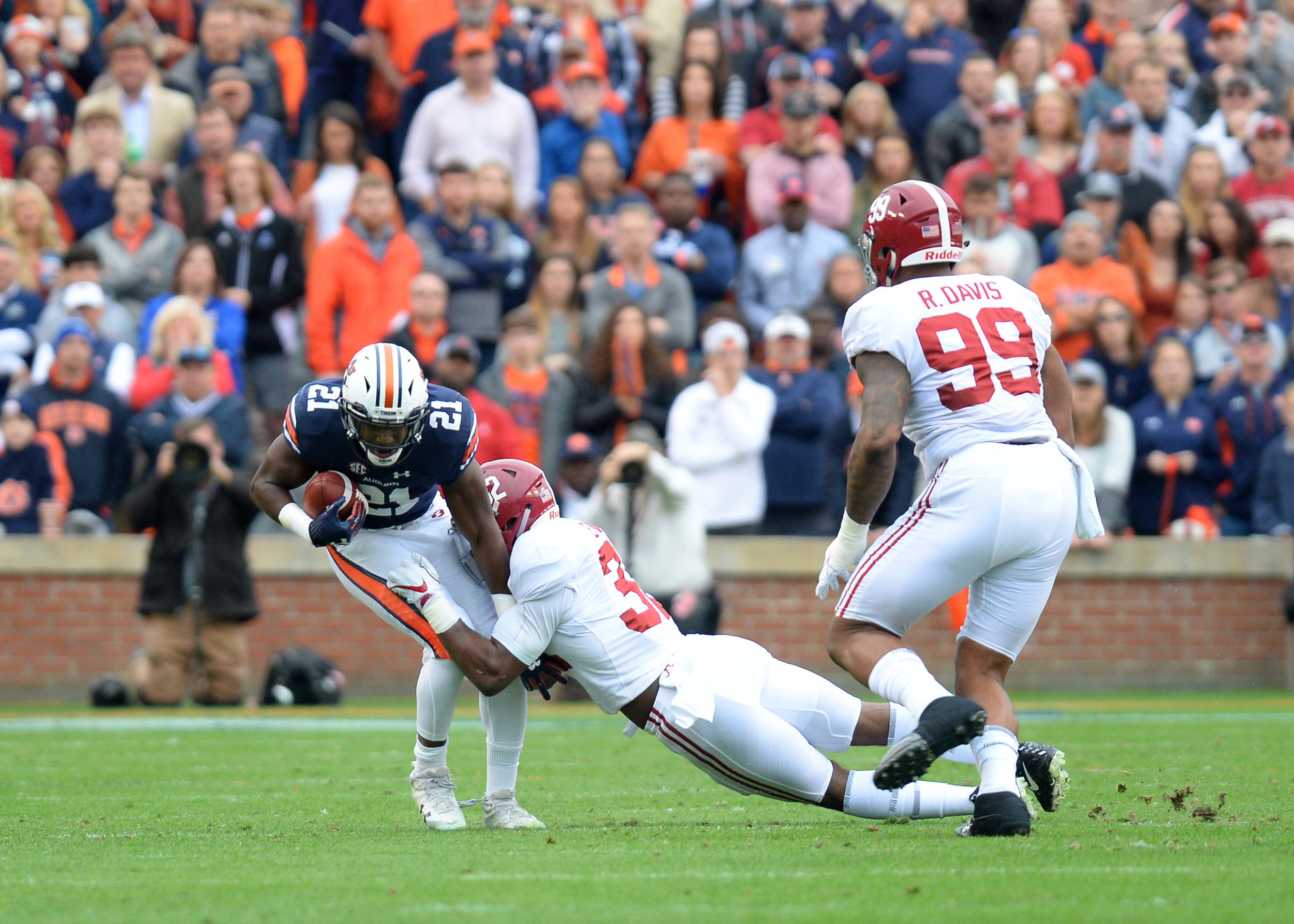 Auburn Tigers running back Kerryon Johnson is tackled by Alabama Crimson Tide linebacker Rashaan Evans (32) during the first half of NCAA football game on Nov. 25, 2017, at Jordan-Hare Stadium in Auburn, Ala. (Photo by Jeff Johnsey)