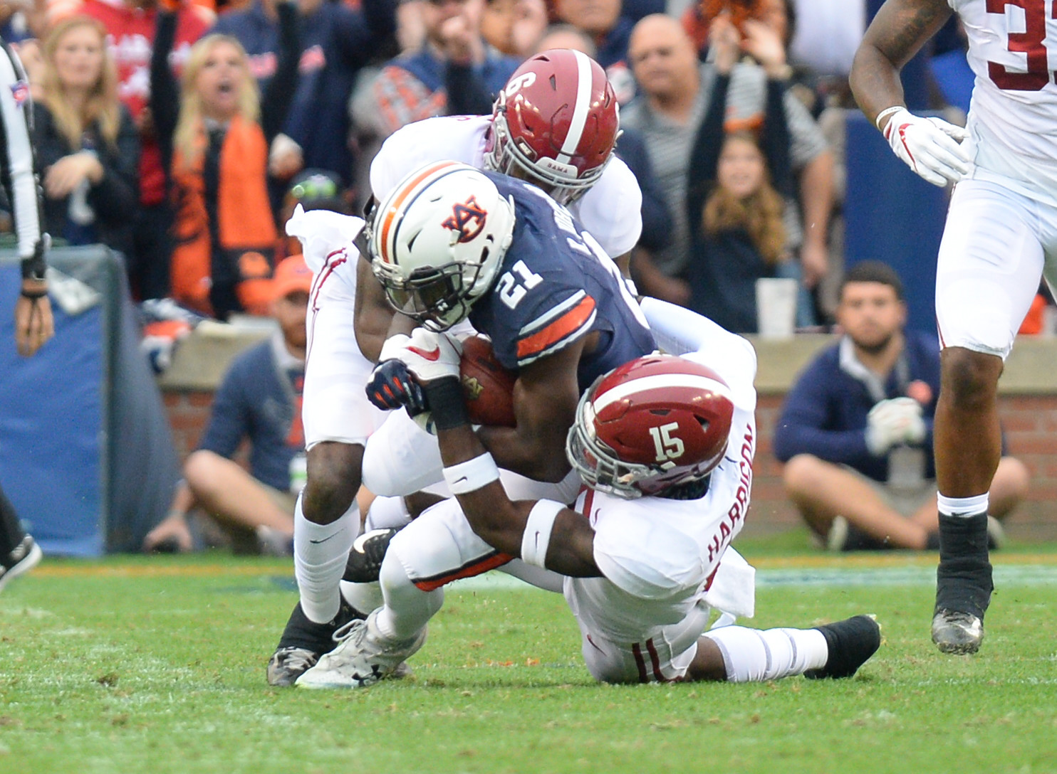Auburn Tigers running back Kerryon Johnson (21) is brought down by Alabama Crimson Tide defensive back Ronnie Harrison (15) and defensive back Hootie Jones (6) during the first half of Saturday's game, at Jordan-Hare Stadium.