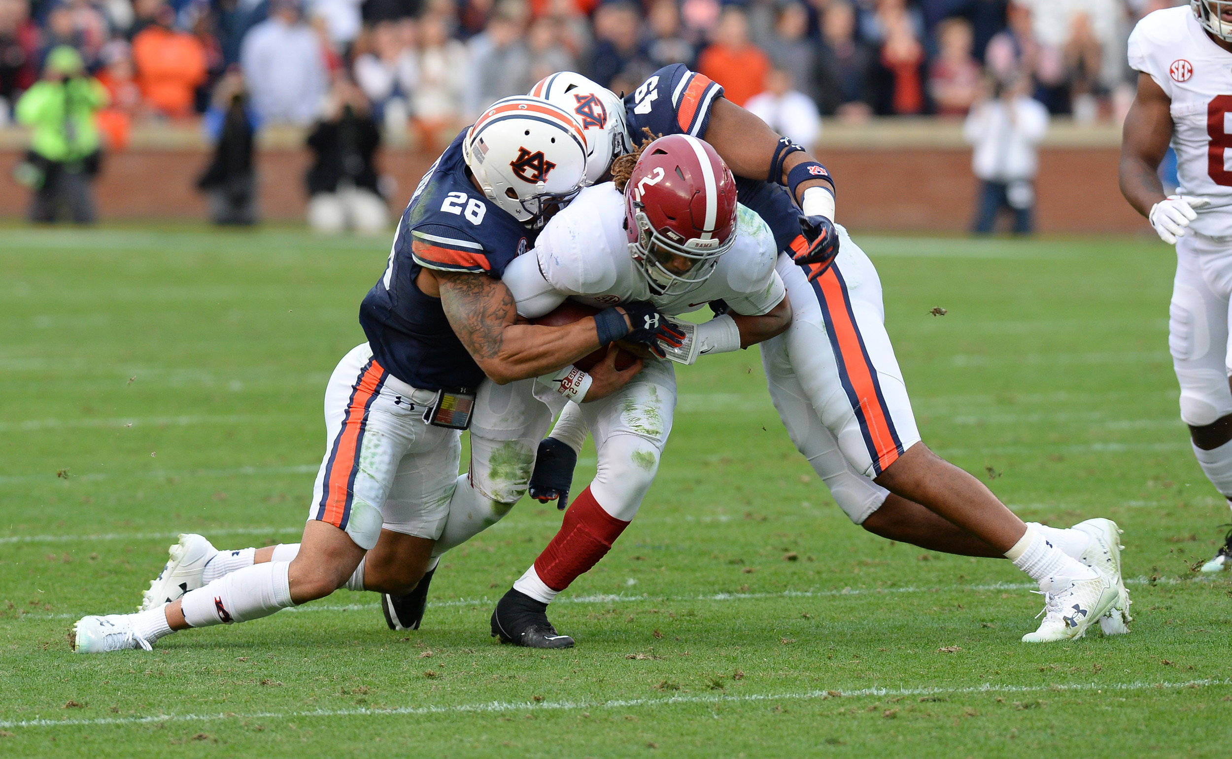 Alabama Crimson Tide quarterback Jalen Hurts (2) is tackled by Auburn Tigers defensive back Tray Matthews (28) and defensive back Jacob Rogers (45)during the first half of Saturday's game, at Jordan-Hare Stadium.