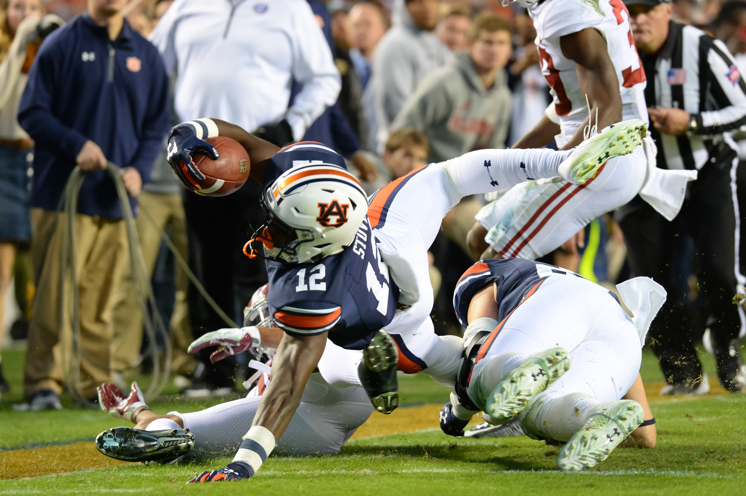 Auburn Tigers wide receiver Eli Stove (12) stretches for extra yardage over Alabama Crimson Tide linebacker Shaun Dion Hamilton (20) during the second half of Saturday's game, at Jordan-Hare Stadium.
