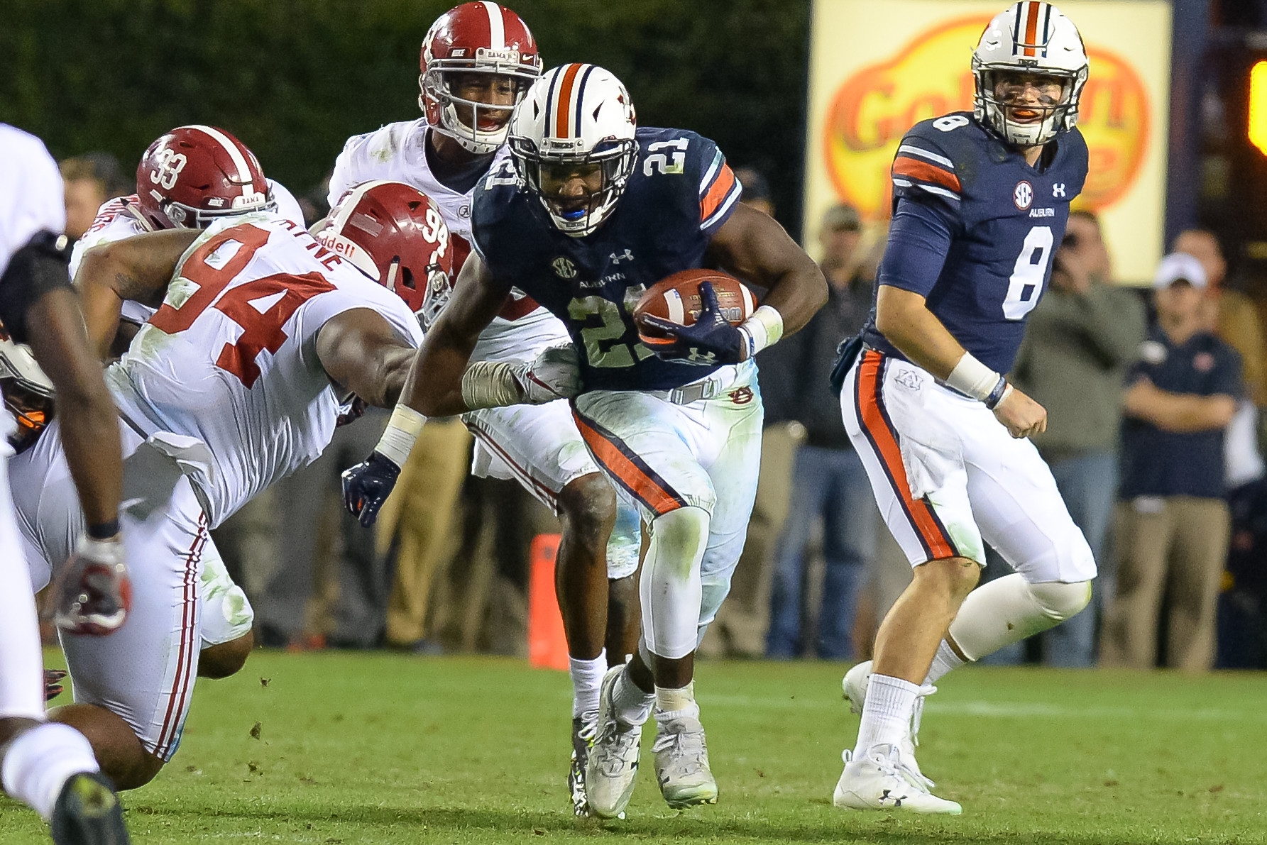 Auburn Tigers running back Kerryon Johnson (21) runs through a tackle of Alabama Crimson Tide defensive lineman Da'Ron Payne (94) during the second half of Saturday's game, at Jordan-Hare Stadium.