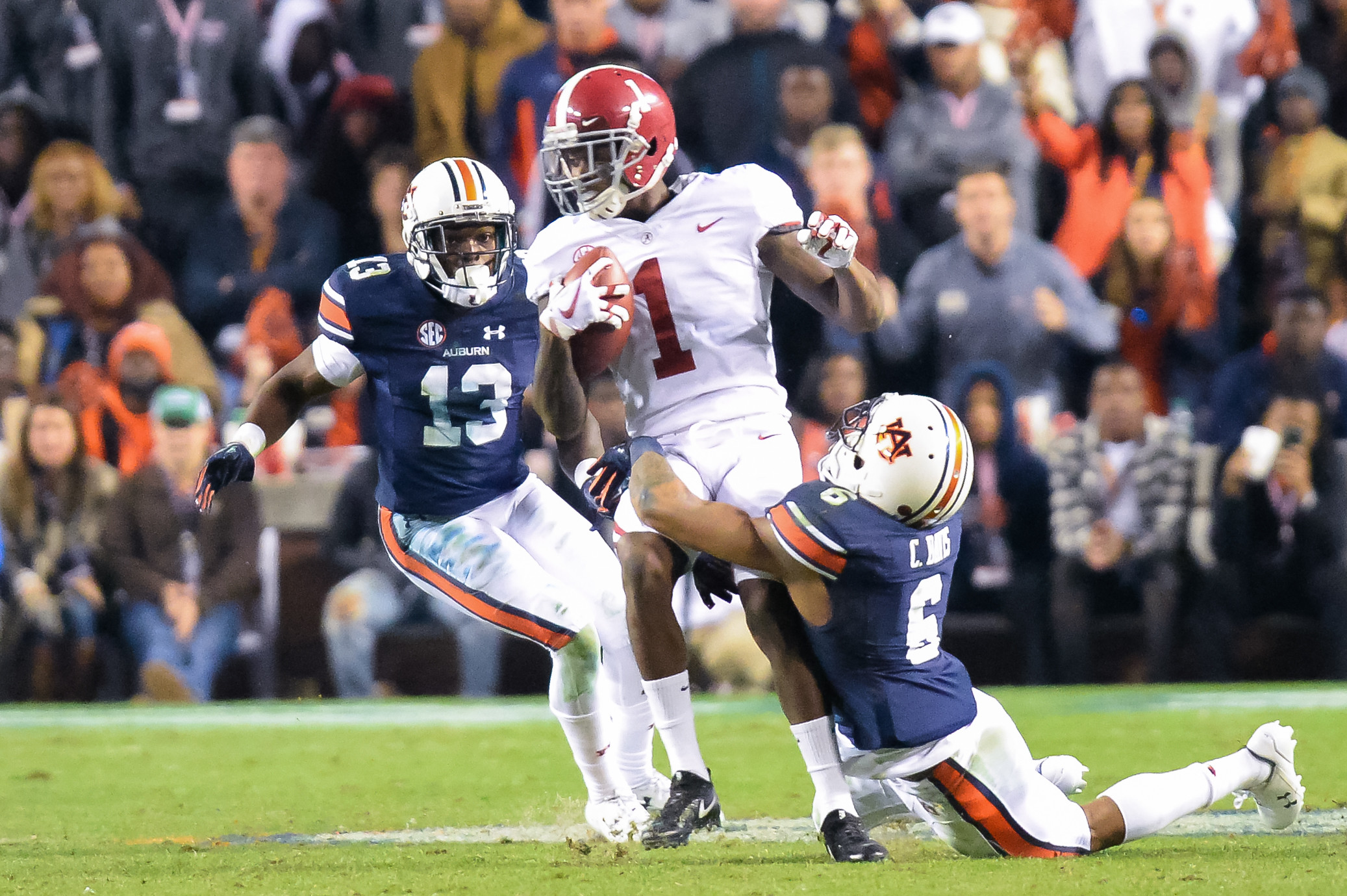 Alabama Crimson Tide wide receiver Robert Foster (1) is tackled by Auburn Tigers defensive back Carlton Davis (6) during the second half of Saturday's game, at Jordan-Hare Stadium.
