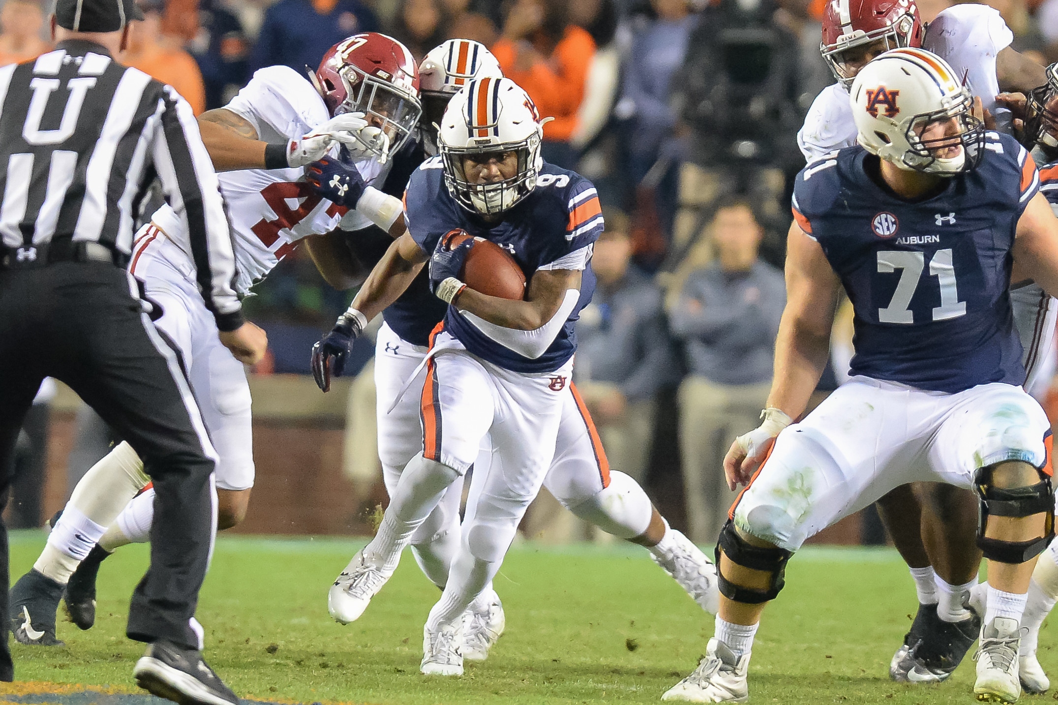 Auburn Tigers running back Kam Martin (9) breaks through the line during the second half of Saturday's game, at Jordan-Hare Stadium.