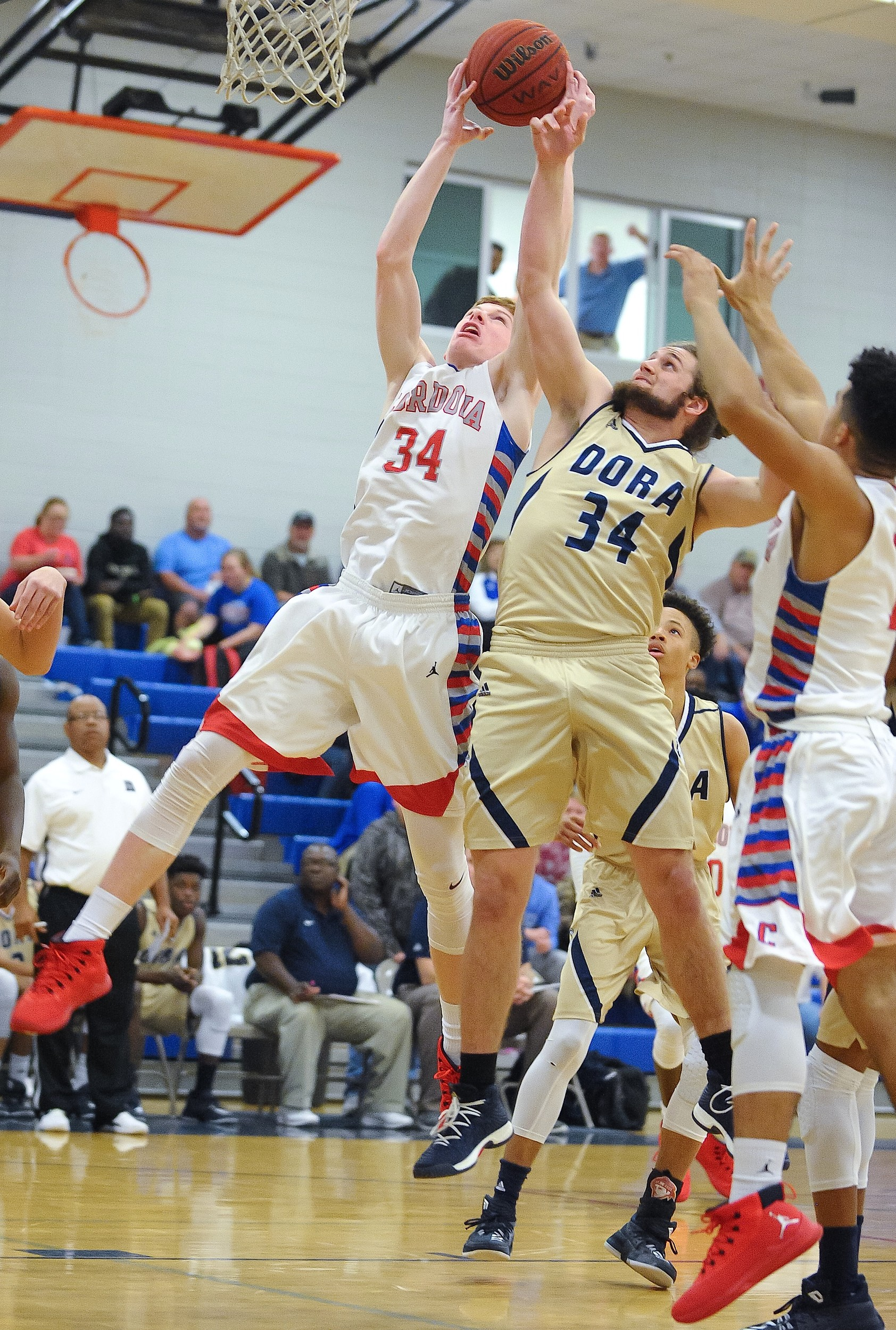 Cordova's Jayce Willingham, left, pulls down a rebound in front of Dora's Noah Roberts, right, during their area game Tuesday at Cordova High School. The Blue Devils won the game 75-60.