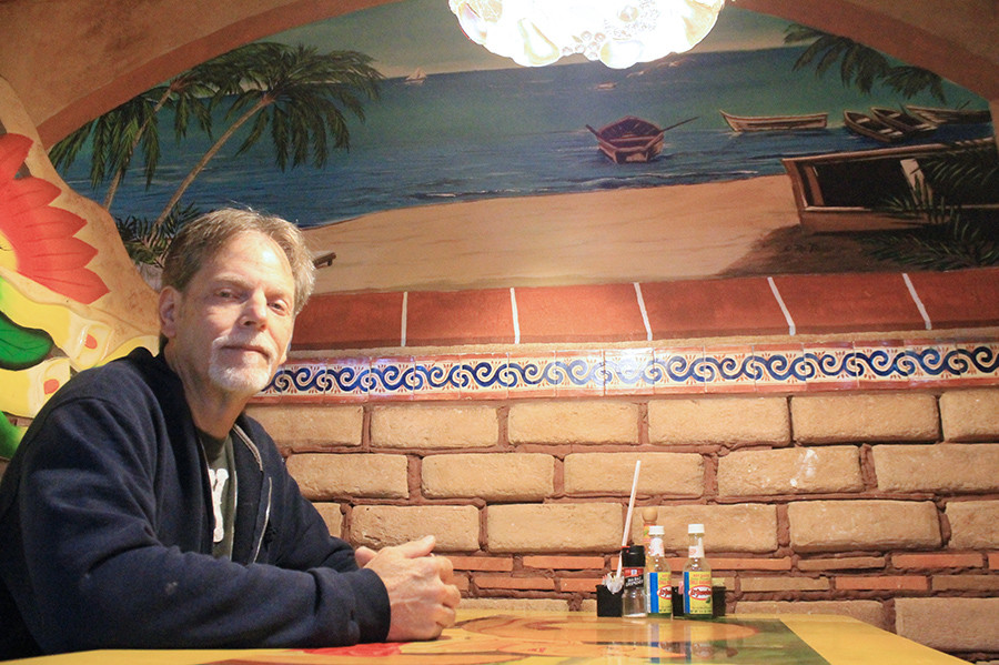 Robert Raburn sits in front of one of the island scenes he has painted at Cabos San Lucas in Jasper. Raburn has also done artwork at the restaturant's location in Haleyville, where he lives.