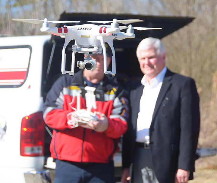 Jasper Mayor David O'Mary looks on as Capt. David Lockhart of the Jasper Fire Department operates a drone used Thursday morning to check blockages along Town Creek.