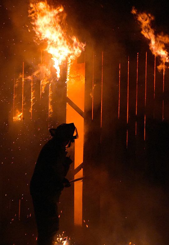 A Jasper firefighter battles the blaze at an abandoned building on Delaware Avenue Tuesday night.