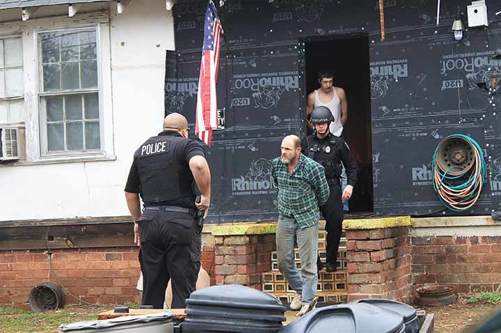 Larry Cox and Ricky Freeman are escorted out of a residence on Jones Street in Cordova Tuesday morning by members of the Cordova Police Department.