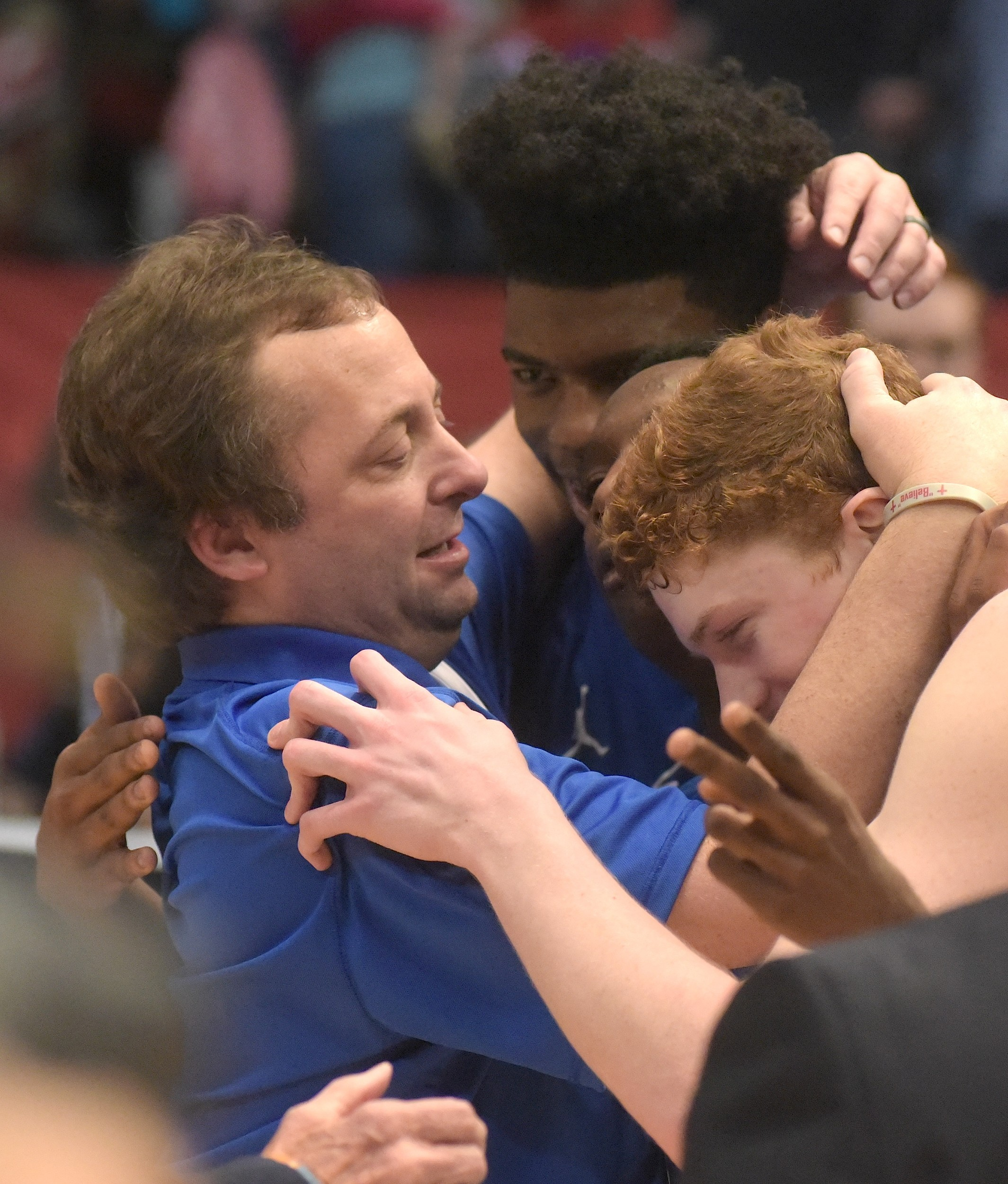 Cordova coach Heath Burns hugs seniors Isaac Chatman, Demetrius Kirk and Jayce Willingham after Friday's state championship win over Madison Academy.