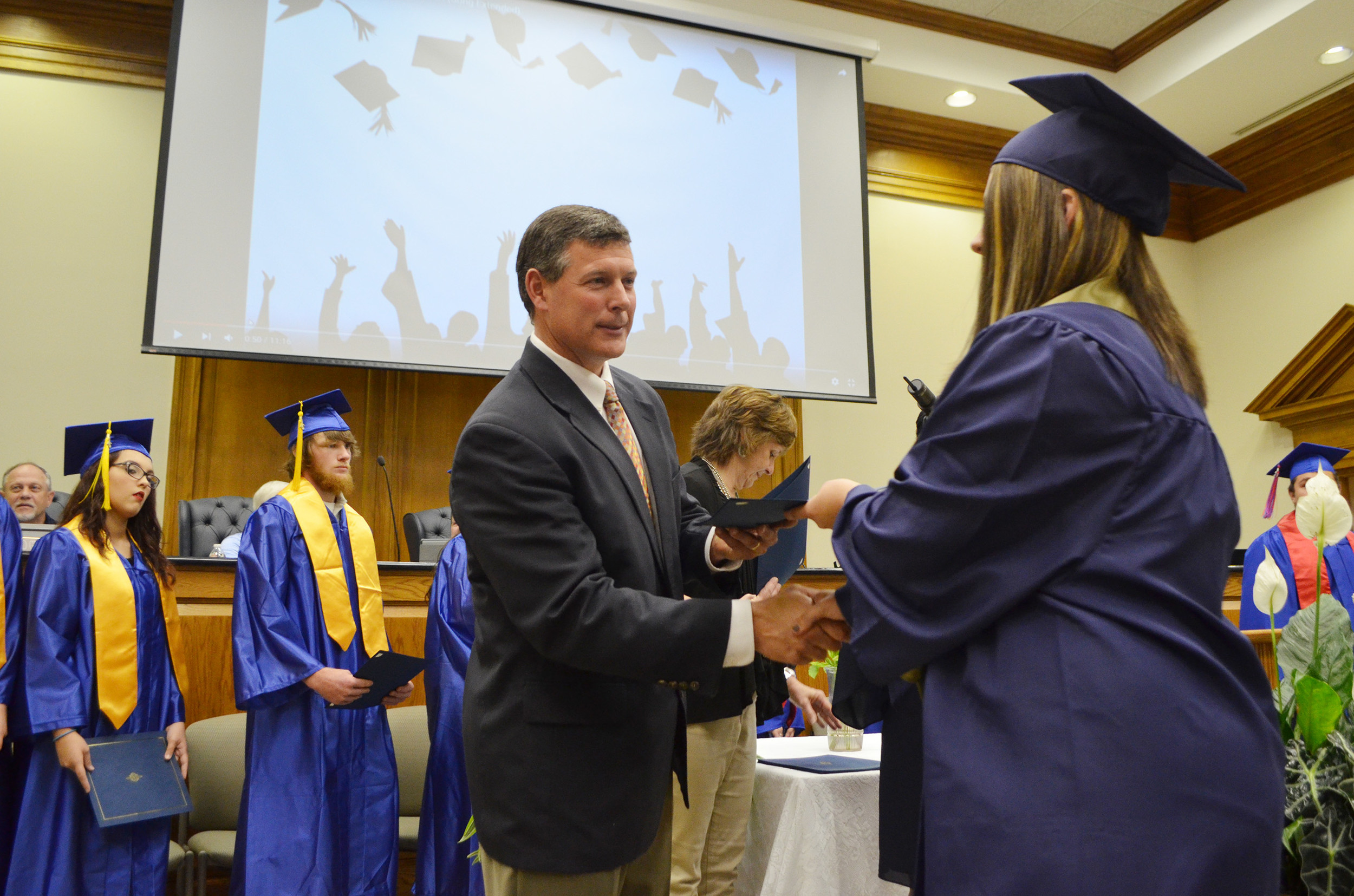 Walker County Schools Superintendent Dr. Jason Adkins presents a diploma to one of the graduates of Twilight Knight School on Thursday evening.  Daily Mountain Eagle - Nicole Smith
