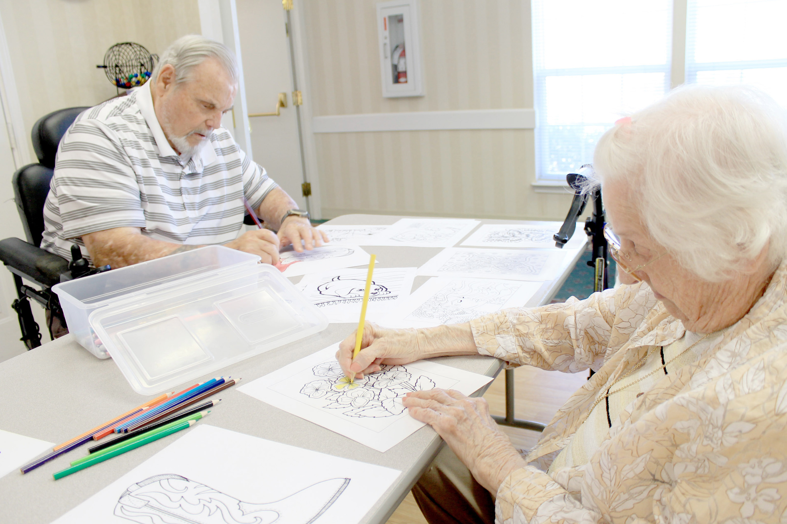 Magdalene Booth and Raymond Muncher work on adult coloring page in the activity room at HarborChase of Jasper Wednesday afternoon. The pastime has been popular with residents since Booth asked life enrichment coordinator Darlene Hubbard to make copies of her coloring book two months ago. Daily Mountain Eagle - Jennifer Cohron