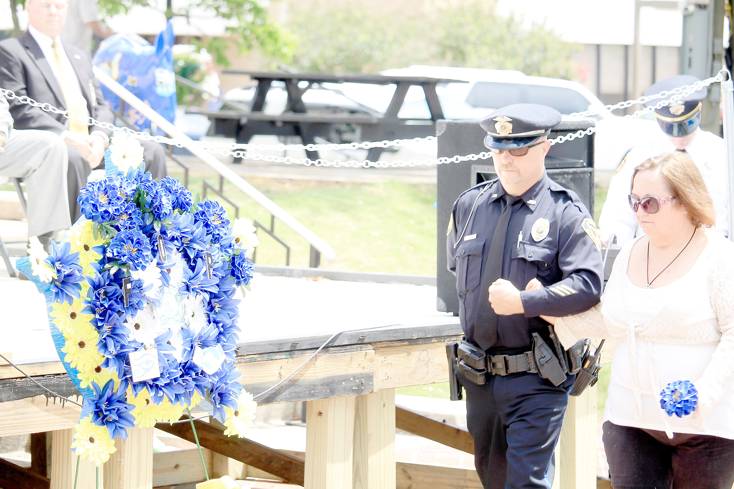 Officer Richard Hobbs, son of James D. Hobbs, escorts his mother, Gale, at the Fraternal Order of Police's annual fallen officer memorial service on Wednesday. James Hobbs' name was recently added to the fallen officers monument at the Walker County Courthouse Square.  Daily Mountain Eagle - Jennifer Cohron