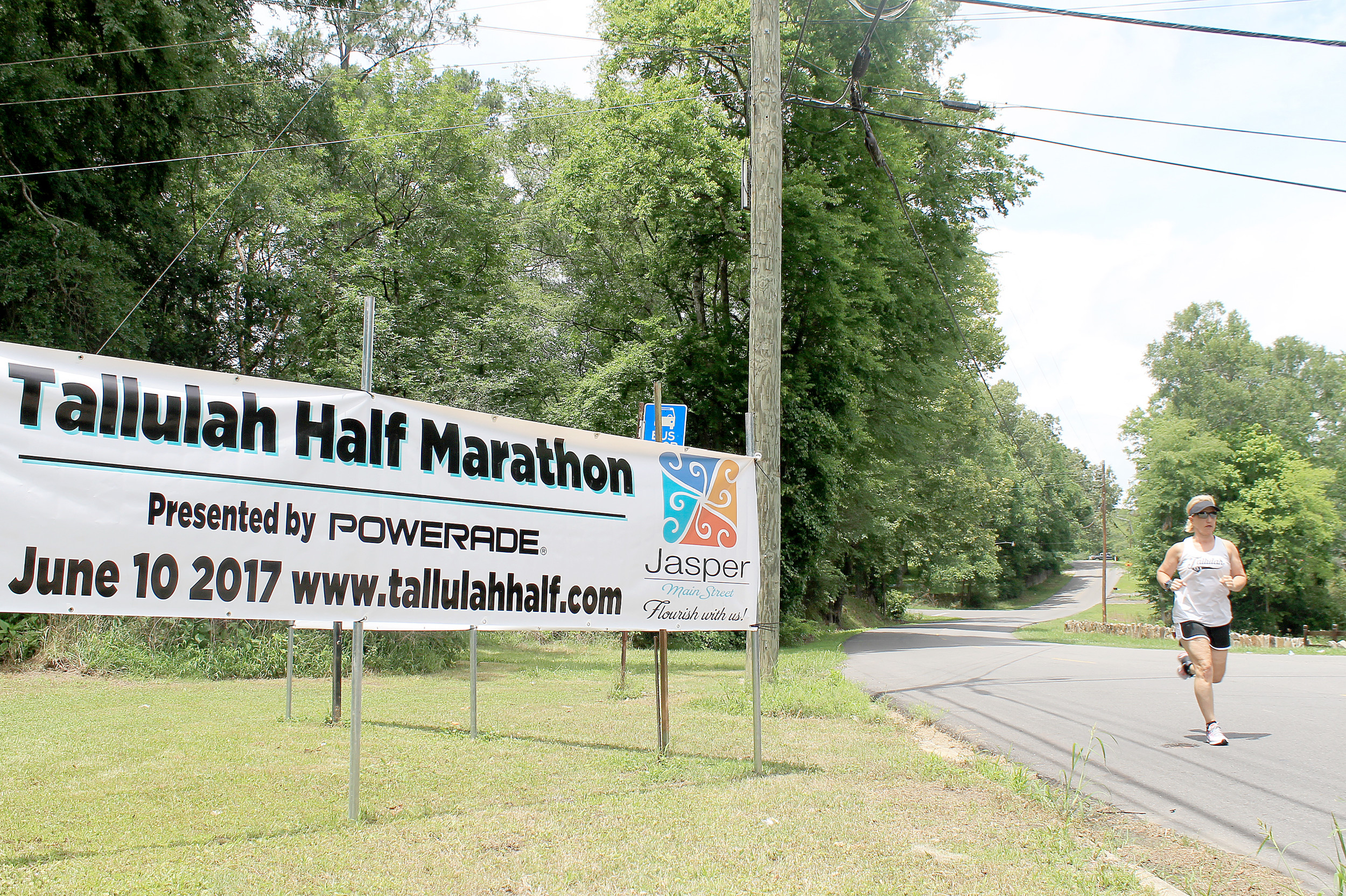 Angela Jo Harris, course director for the Tallulah Half Marathon, runs past a sign on Third Avenue advertising the event. Harris is also overseeing the Kids Half Marathon, a new event added to the third annual Tallulah Bankhead Tribute. Daily Mountain Eagle - Jennifer Cohron
