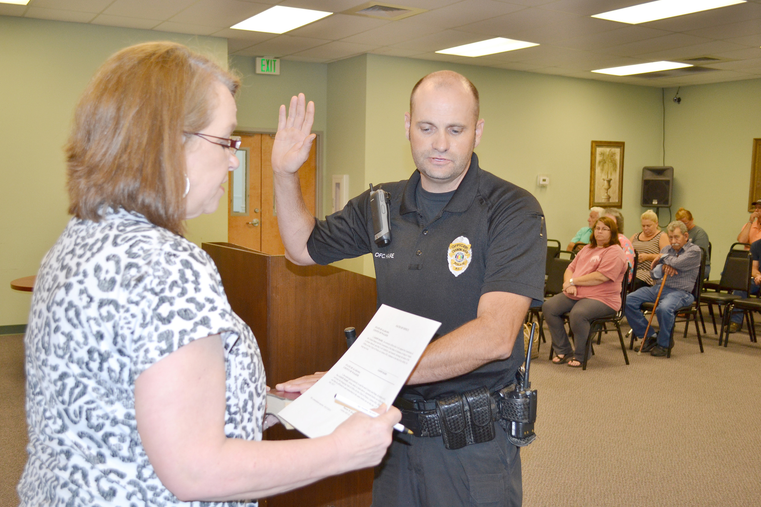 Jason Hare is sworn in by City Clerk Nanette Brown immediately after the Carbon Hill City Council approved Hare Thursday to be the city's new police chief. Daily Mountain Eagle - Ed Howell