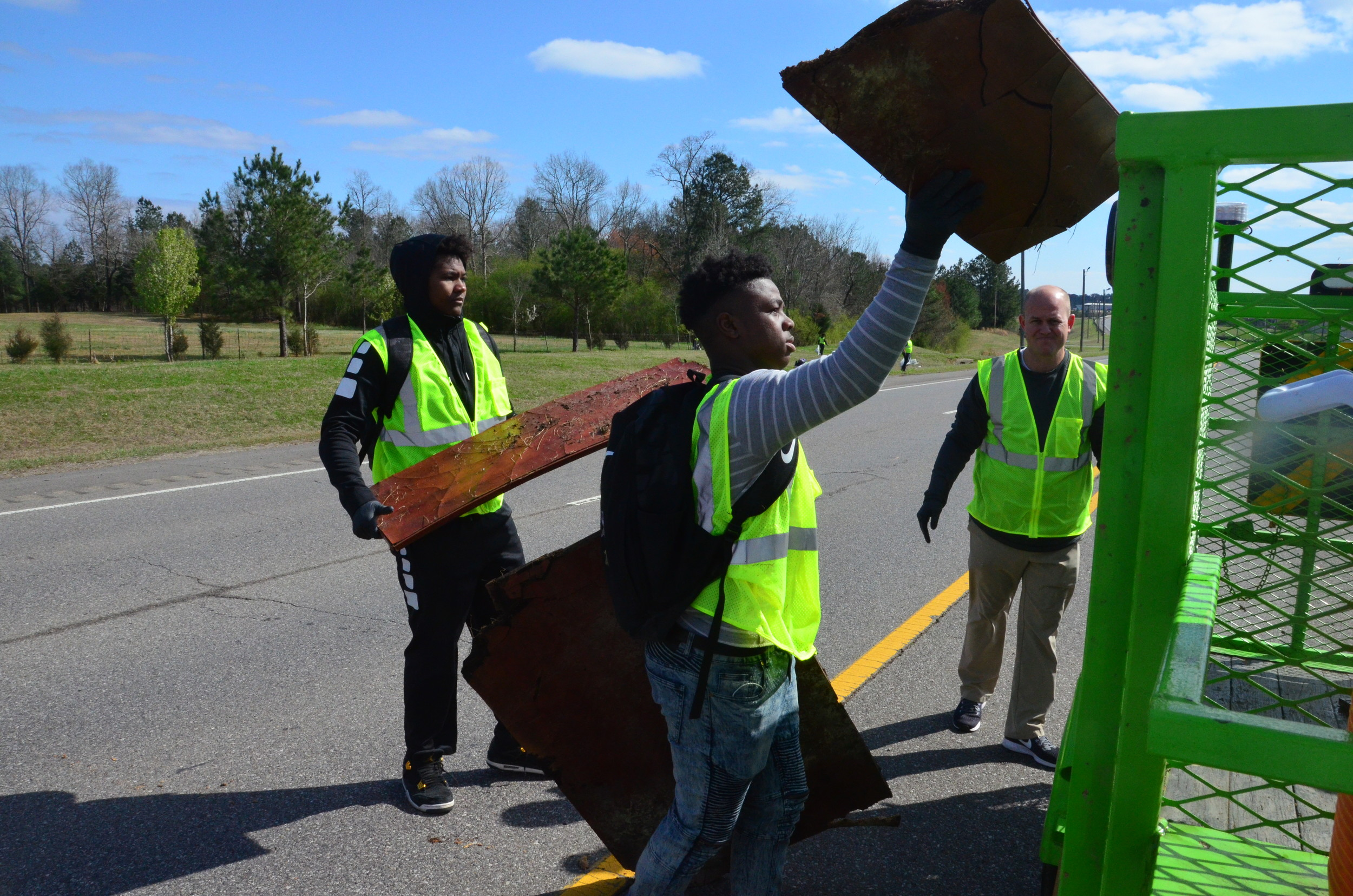 Jasper High football players and head coach Bryan Moore load trash into the city's Clean as a Whistle trailer.