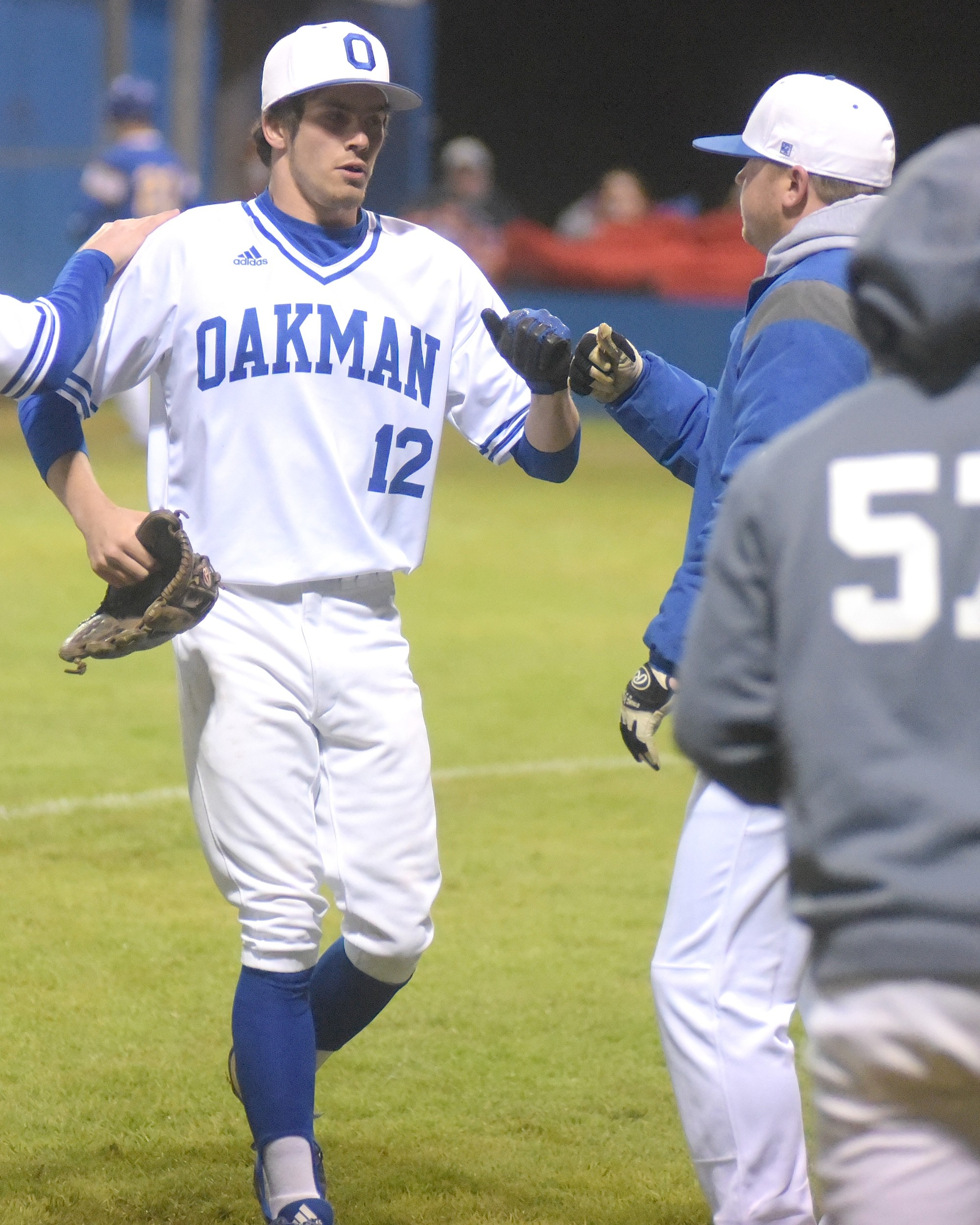 Oakman's CJ Hall (12) is greeted by coach Caleb Hoyle after retiring the Curry Yellow Jackets in the second inning Thursday. Hall tossed a two-hitter, striking out 12 baters as Oakman earned the Walker County Baseball Tournament title with an 8-0 win at Curry High School.