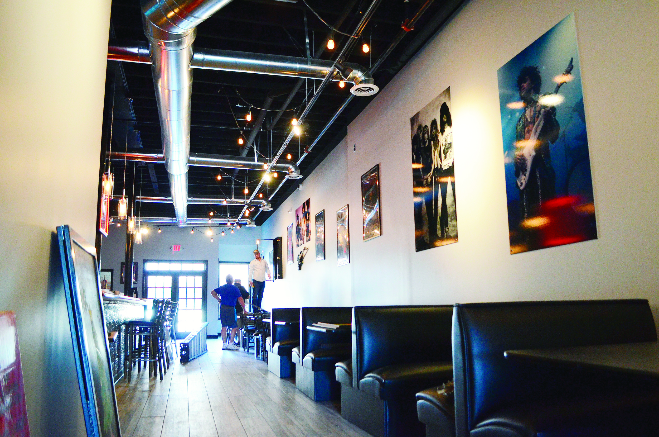 The interior of Rock N Roll Sushi is decorated with photographs of rock stars and other rock themed items.
