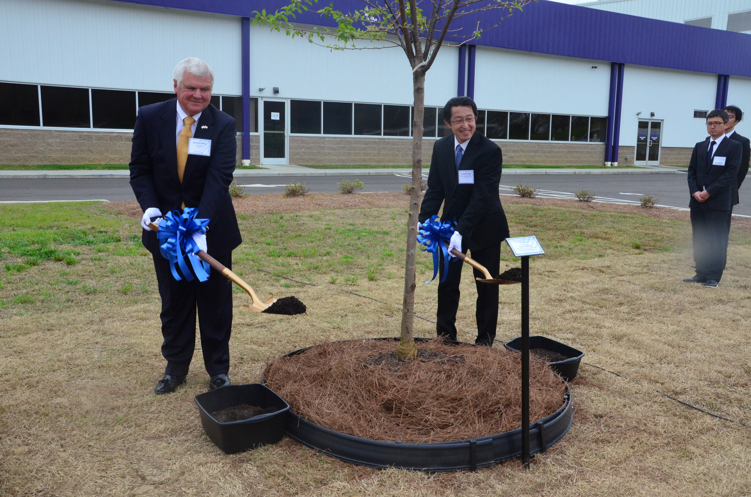 Jasper Mayor David O'Mary and Toshiyuki Yago, president of Yorozu Automotive Alabama, participate in a tree planting ceremony Tuesday at the Yorozu location in Jasper.