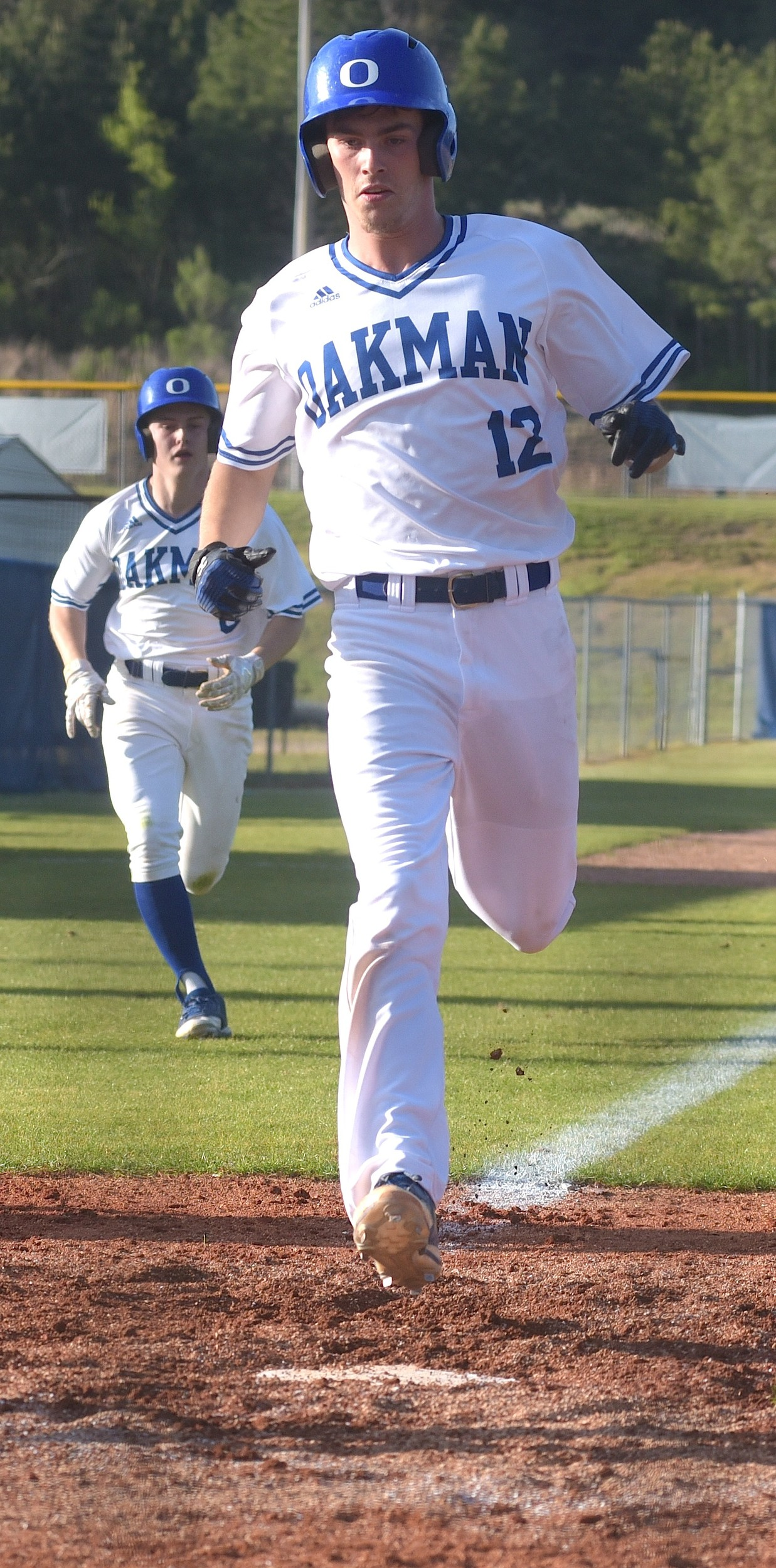 Oakman's CJ Hall (12) and Dylan Norris (6) score on JonDawson Tittle's three-run double on Tuesday in a 7-5 win over Carbon Hill.