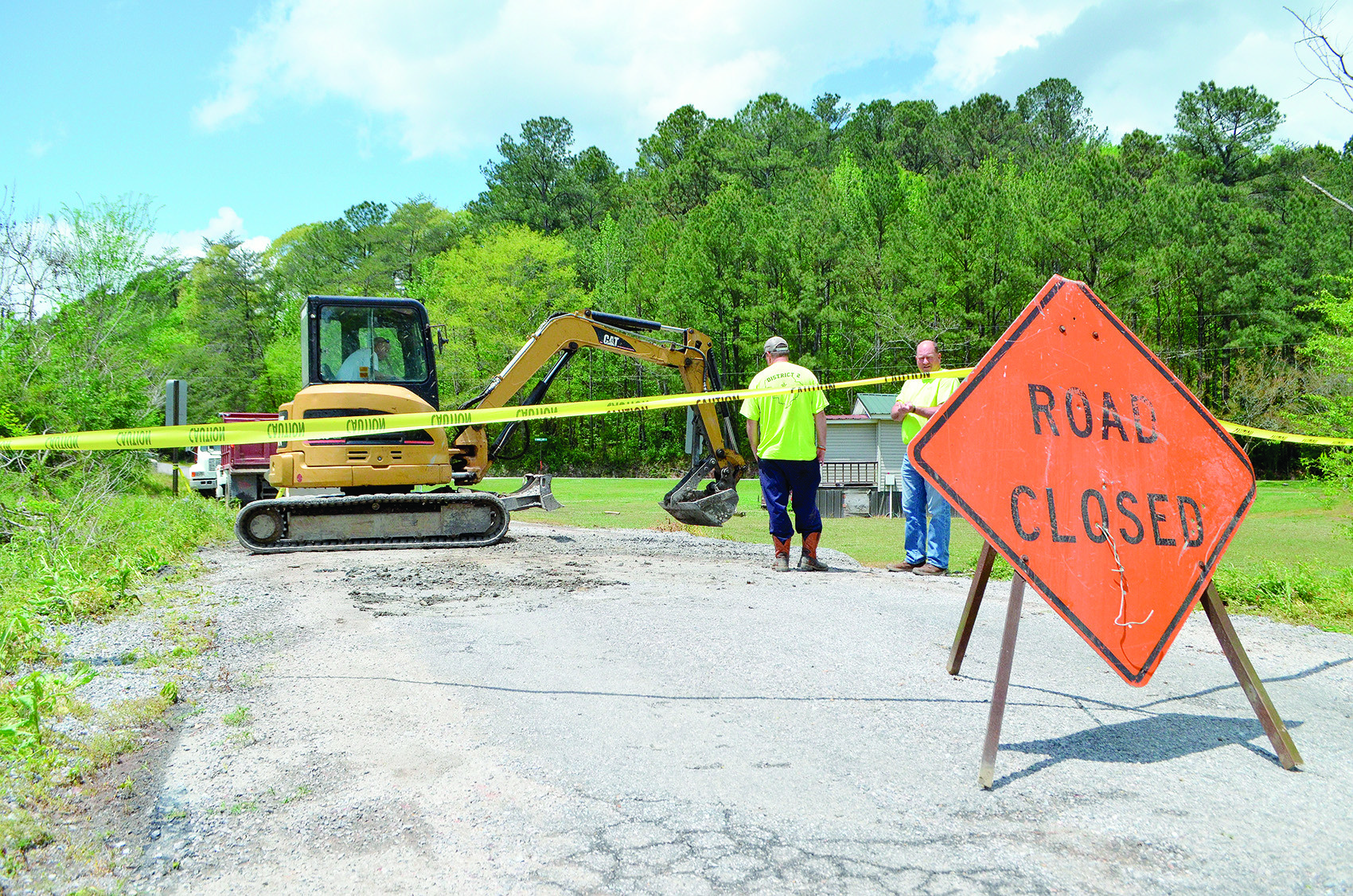 Crews worked Monday to patch an area of road near the intersection of School Street and Swindle Loop Road in Oakman that was washed out by floodwaters Sunday evening.