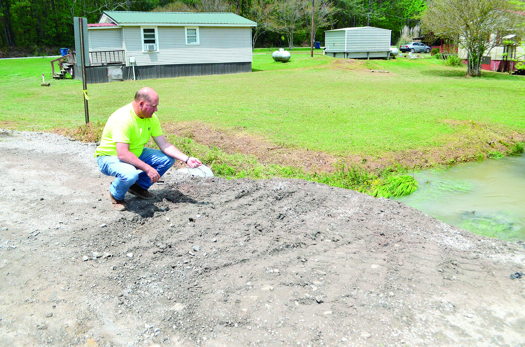 Walker County District 2 Commissioner Jeff Burrough, pictured, explains that torrential rains caused a creek to overflow Sunday. The culvert, below School Street, couldn't accommodate the water's rise and washed out the street.