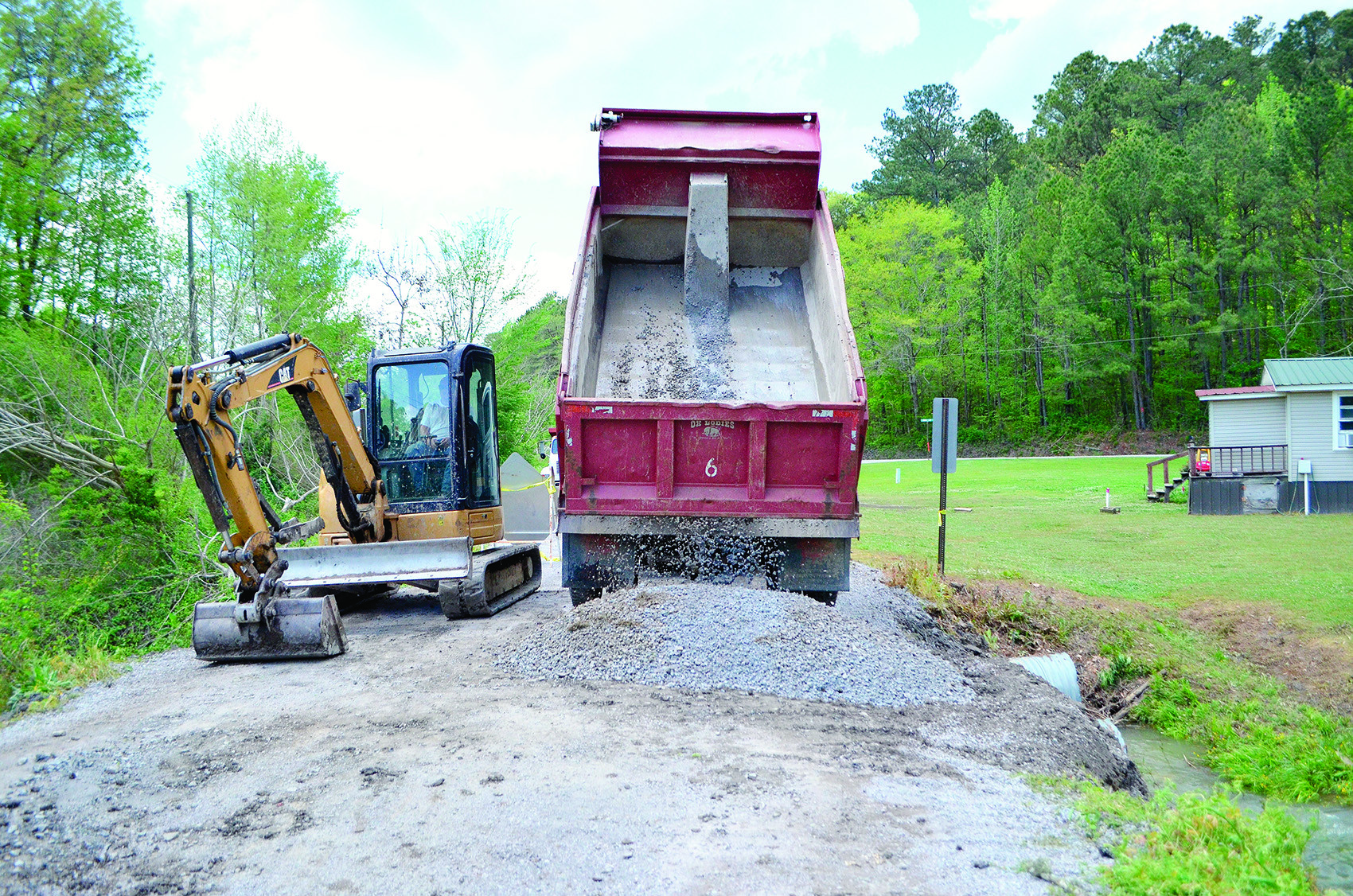 Paving material is poured to help patch a section of School Street Monday that was washed out by downpours Sunday.