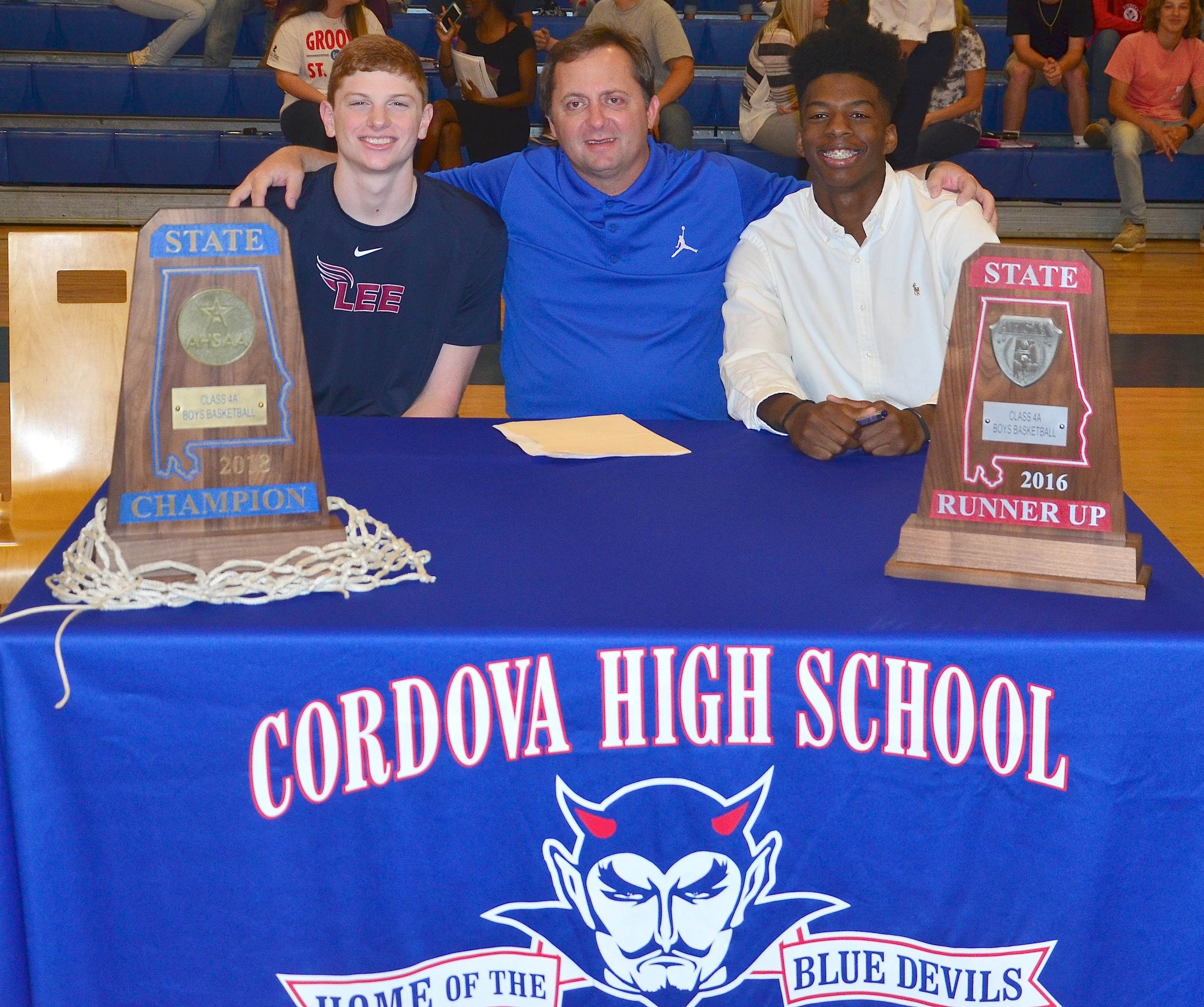 Cordova basketball coach Heath Burns sits between Jayce Willingham, left, and Isaac Chatman, right, after both players signed letters-of-intent on Thursday at the school. Willingham signed with Lee University, a Division II school in Tennessee, while Chatman signed with Campbell University, a Division I school in North Carolina. Both players helped lead Cordova to the Class 4A state title in March.