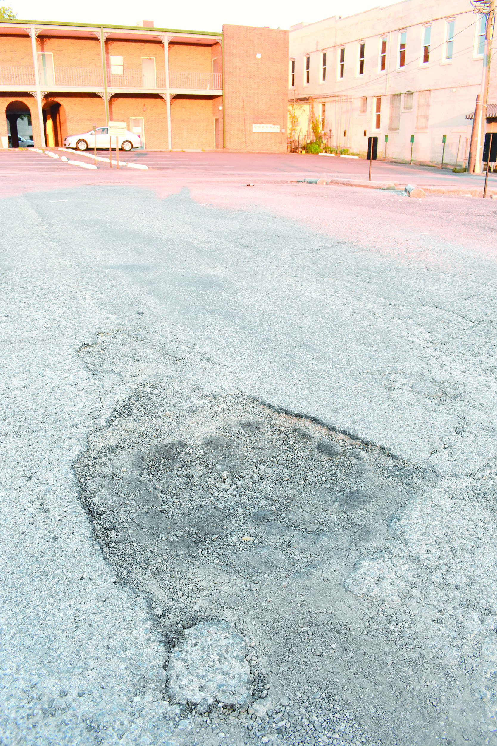 This pothole shows why the city is paving its parking lot behind a number of attorney offices in downtown Jasper. The city has announced a list of paving projects, using bond money it obtained last year.