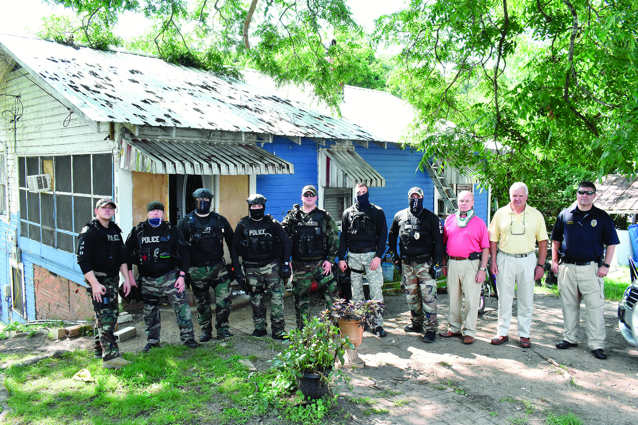 Jasper Police Department officers and Mayor David O'Mary stand in front of a house in Frisco that was the scene of  a drug bust Wednesday morning. O'Mary said he wanted to honor the department for their work on the case. One suspected drug dealer was arrested.