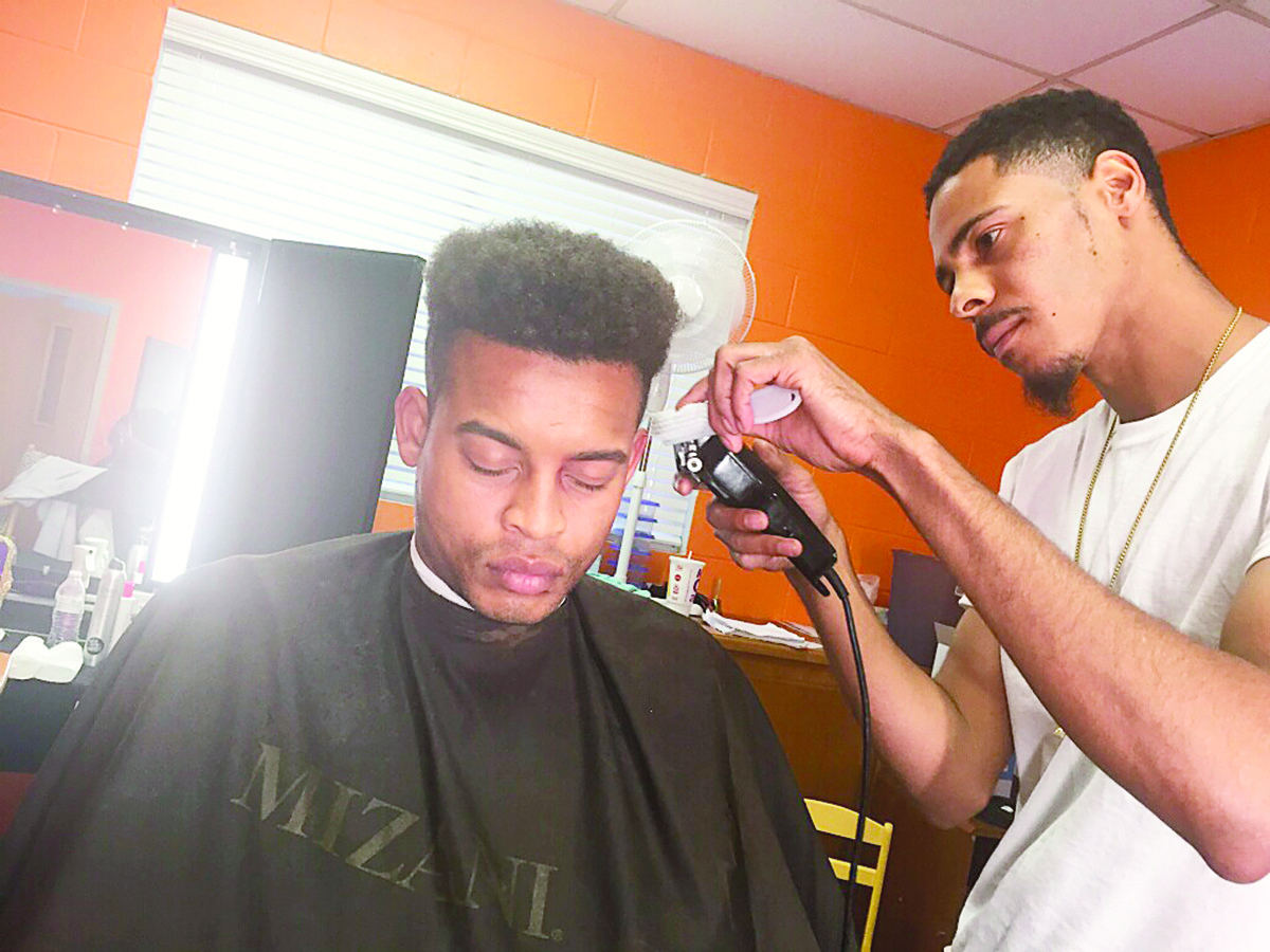 "Jason Walker cuts the hair of actor Robert Ri'chard on the set of ""My Brother's Keeper"" in June. Walker, a graduate of Walker High School, is finally realizing his dream of being a celebrity barber and is also working on other goals such as barber's clothing line and barber arts seminars."