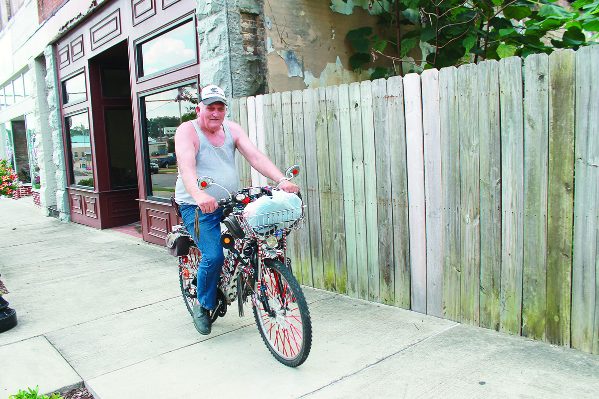 Lewis Ray Johnson rides his bike through downtown Jasper. He has spent several years making it his own by adding with dozens of lawn chair leg tips, whiskey bottle corks and strips of red reflective tape to the bike's frame.