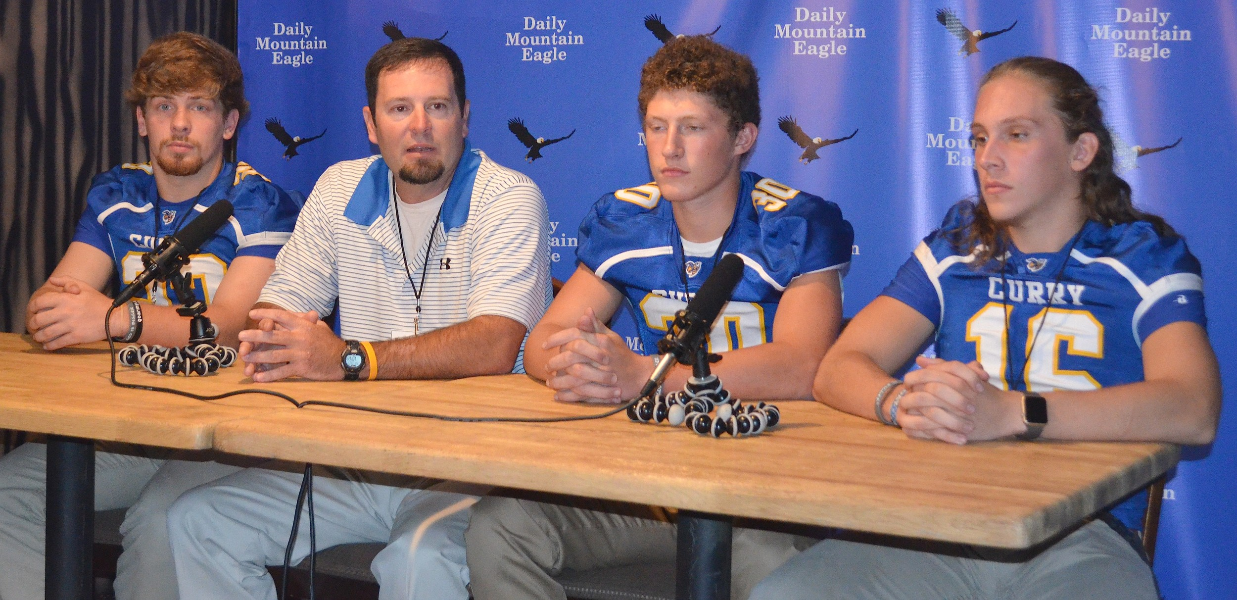 Curry coach Philip Smith sits with players, from left, Tristan Jones, Colton Burton and Austin Patton during Walker County Football Media Day on Friday.