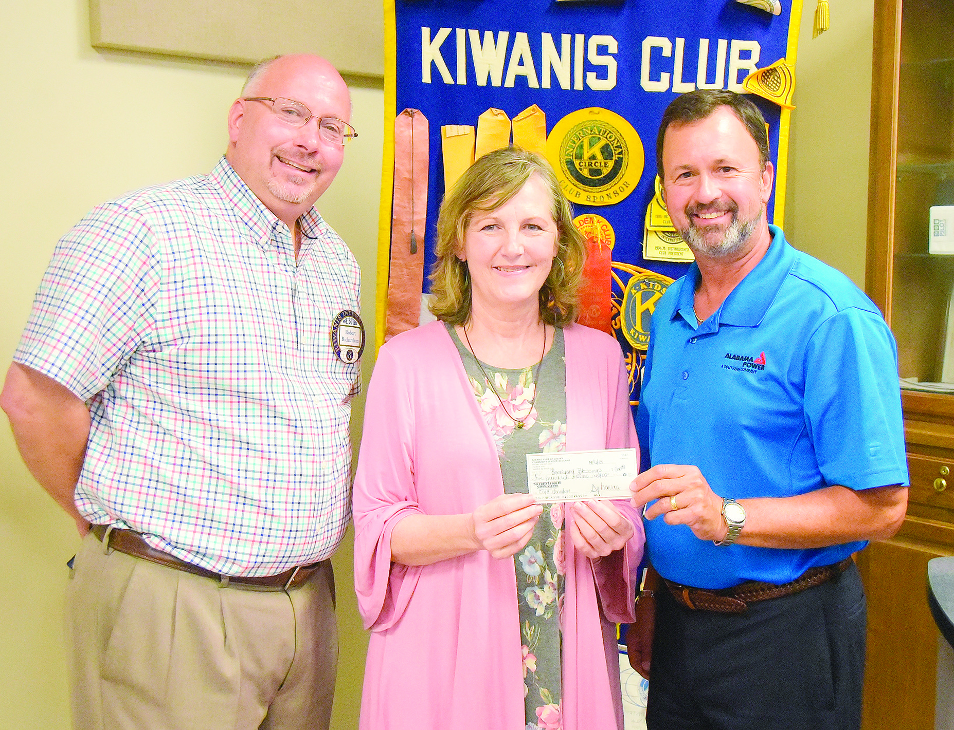 Robert Richardson, at left, and Billy Doss, at right, of the Kiwanis Club of Jasper present a donation to Leneda Jones of Backyard Blessings to be used to help with operating expenses for the organization that helps feed students throughout Walker County.