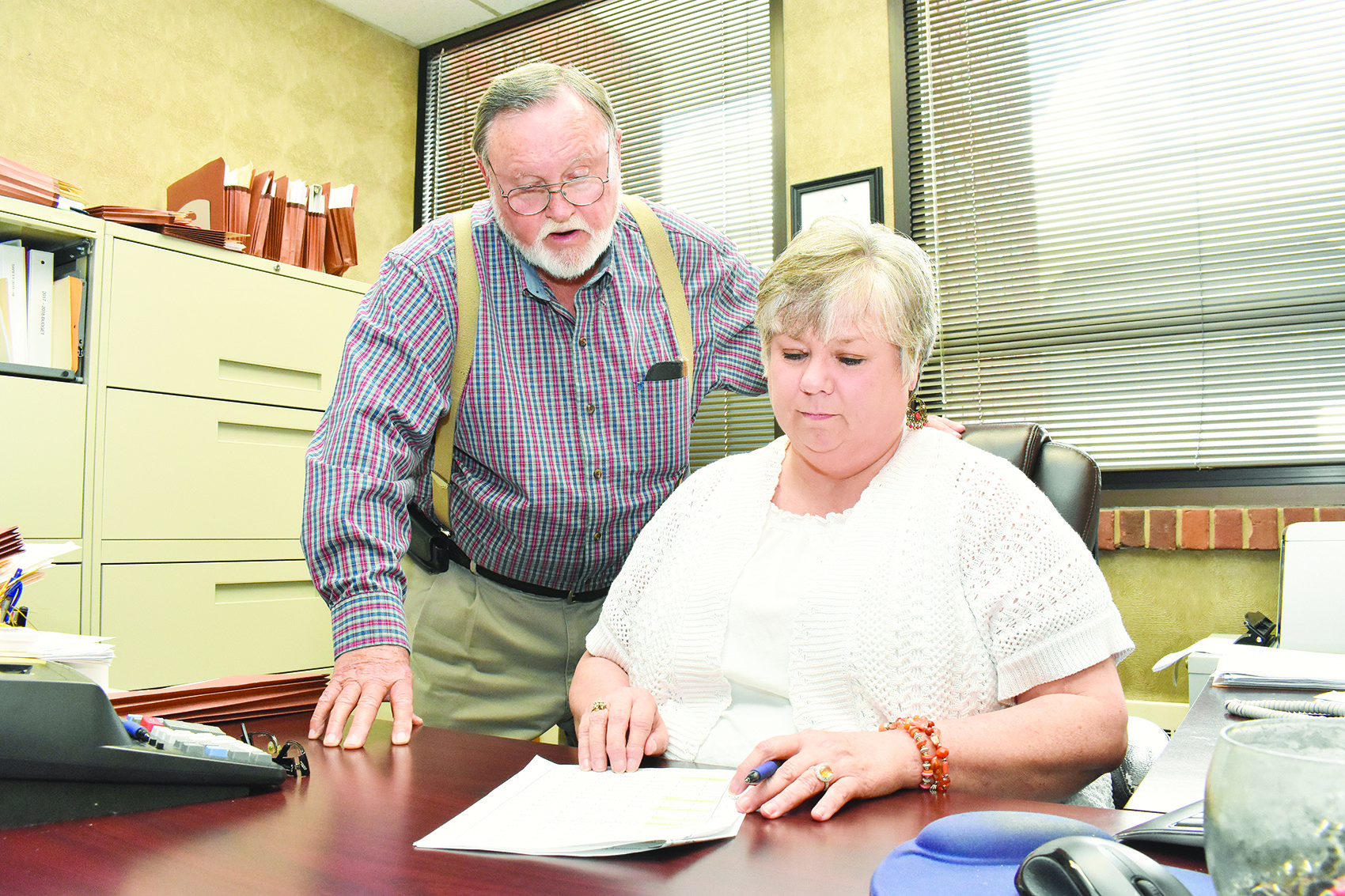 Walker County Administrator Robbie Dickerson shows some financial figures to Walker County Commission Chairman Jerry Bishop in her office recently. Dickerson has become the permanent county administrator after serving on an interim basis since January.