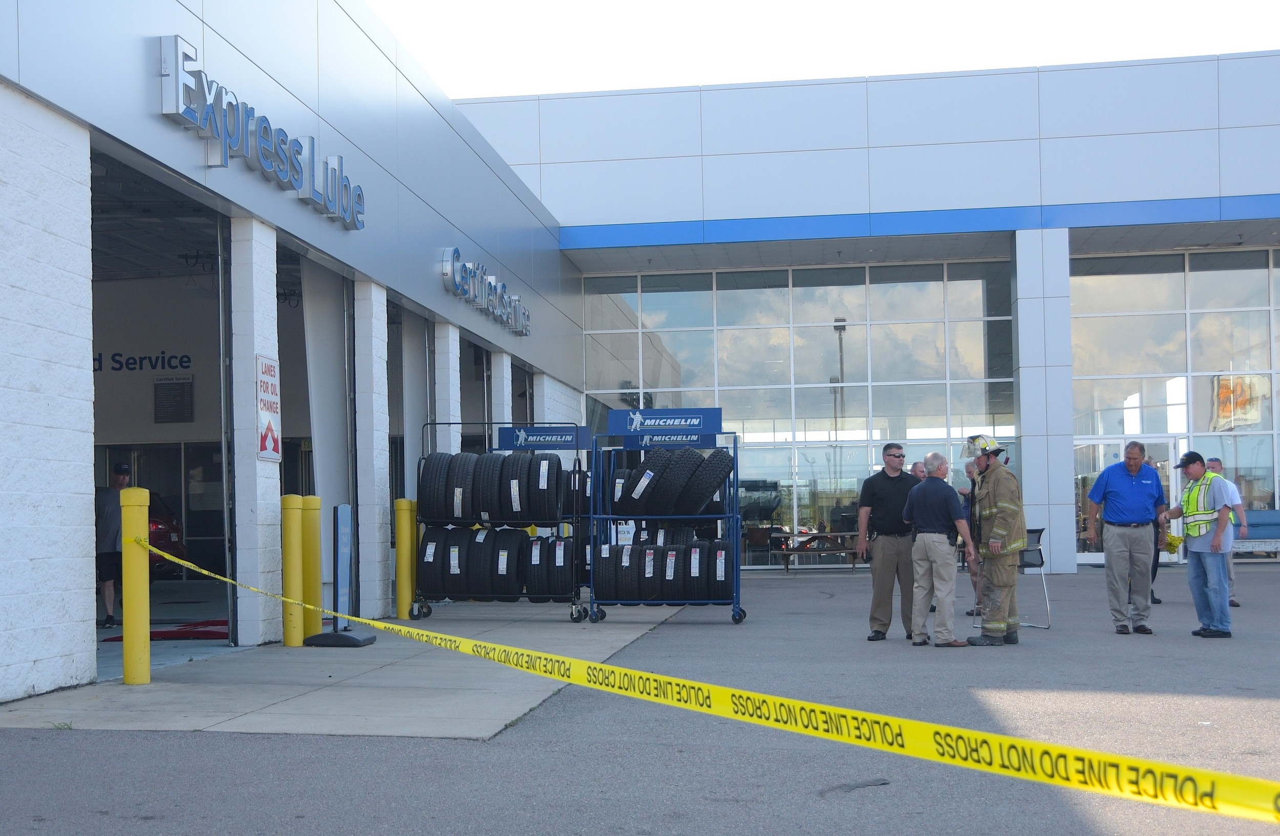 Emergency personnel talk outside the service department where a flash fire fatally injured three Carl Cannon Chevrolet employees in June 2017.