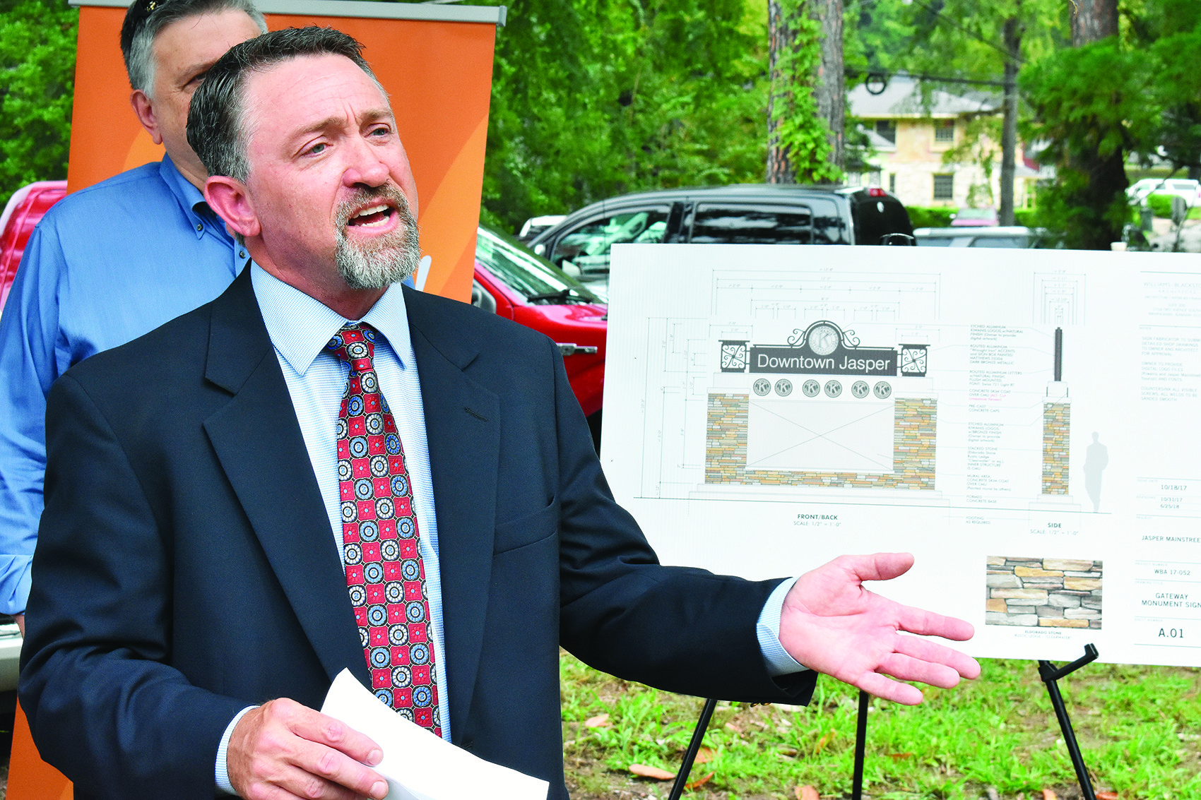Todd Thompson of the Jasper Kiwanis Club speaks Friday near a rendering of the new Downtown Jasper sign to be in a new pocket park. Officials broke ground on the Kiwanis project Friday. Thompson was a coordinator for the project.