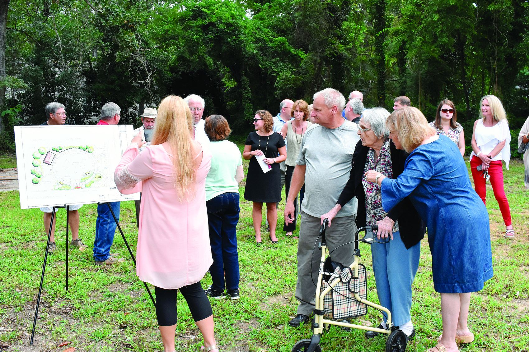 Louise Wade (with the walker), the widow of former Probate Judge Stanley A. Wade, is assisted while looking at a proposed drawing of a pocket park that is being named in honor of her husband, who died Thursday. The groundbreaking was held Friday.