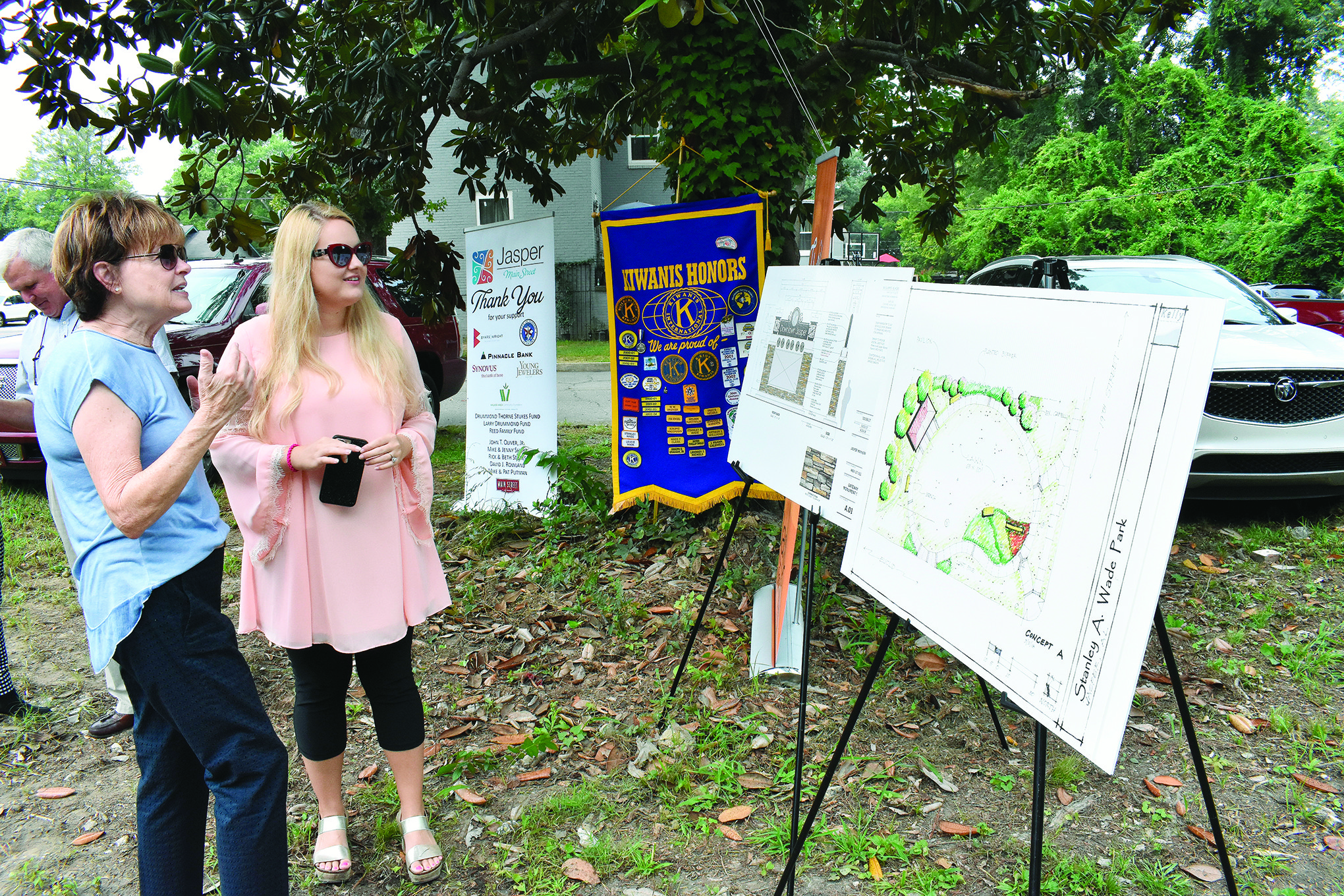 Helen Louise Wade Johnson, far left, looks on Friday at drawings for a new Jasper pocket park and Downtown Jasper welcome sign. The park will be named after her father, former Probate Judge Stanley A. Wade, who died on Thursday. The drawings were set up at a groundbreaking for the park, which has been a project of the Jasper Kiwanis Club.