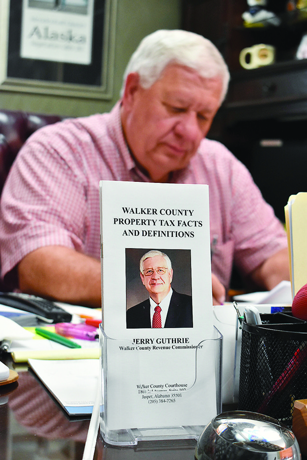 Walker County Revenue Commissioner Jerry Guthrie works at his desk with brochures displayed that go into great detail about property taxes, including exemptions for those past age 65.